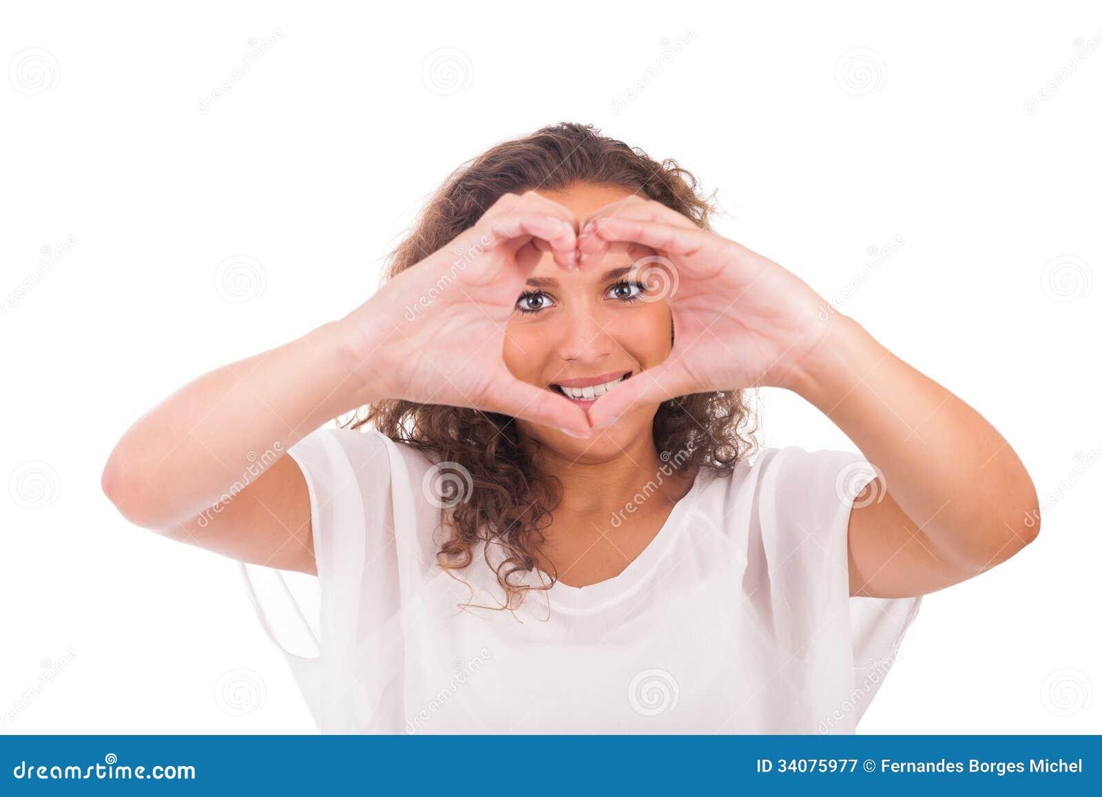 Härlig ung kvinna som gör en hjärta med händer