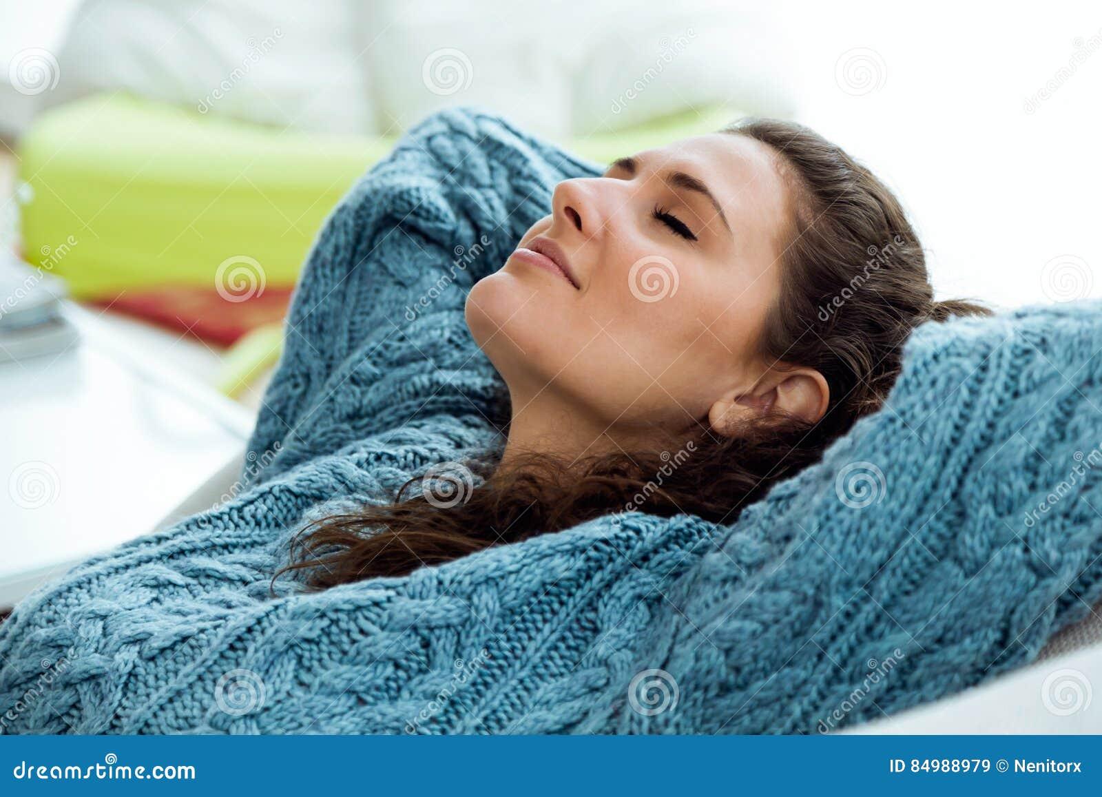 Härlig ung kvinna som hemma kopplar av på soffan