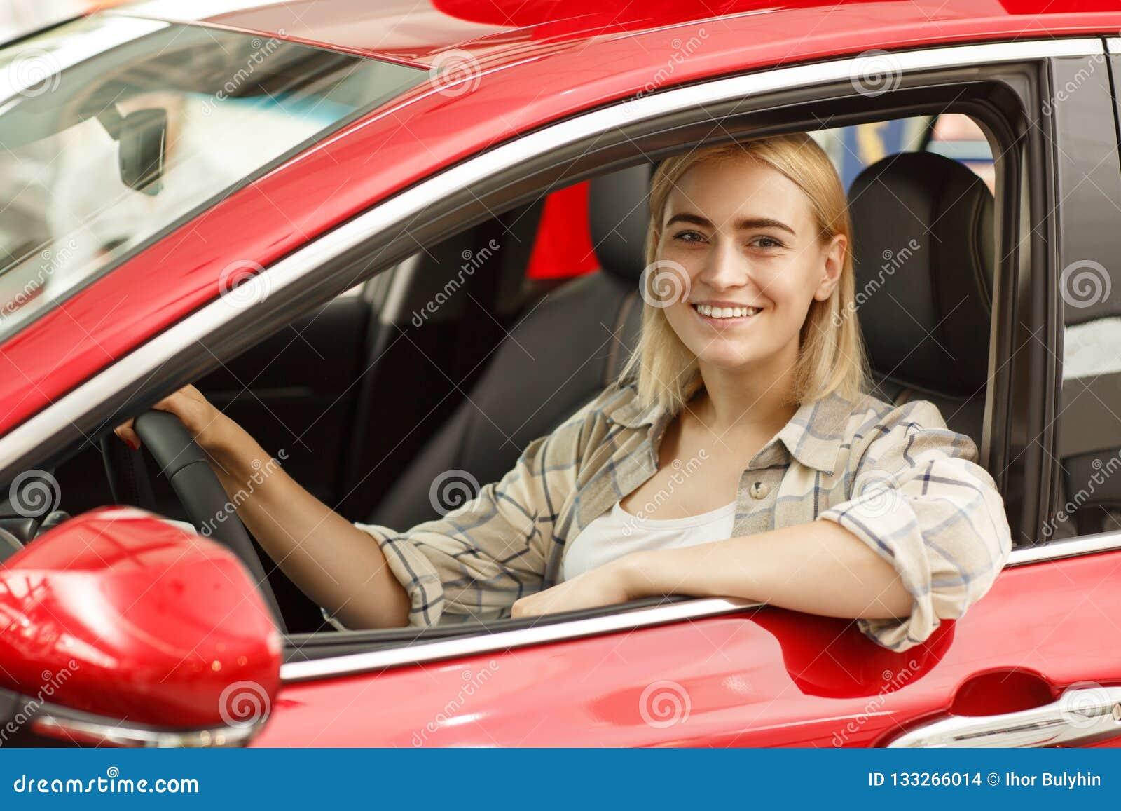 Härlig ung kvinna som köper den nya bilen på återförsäljaren