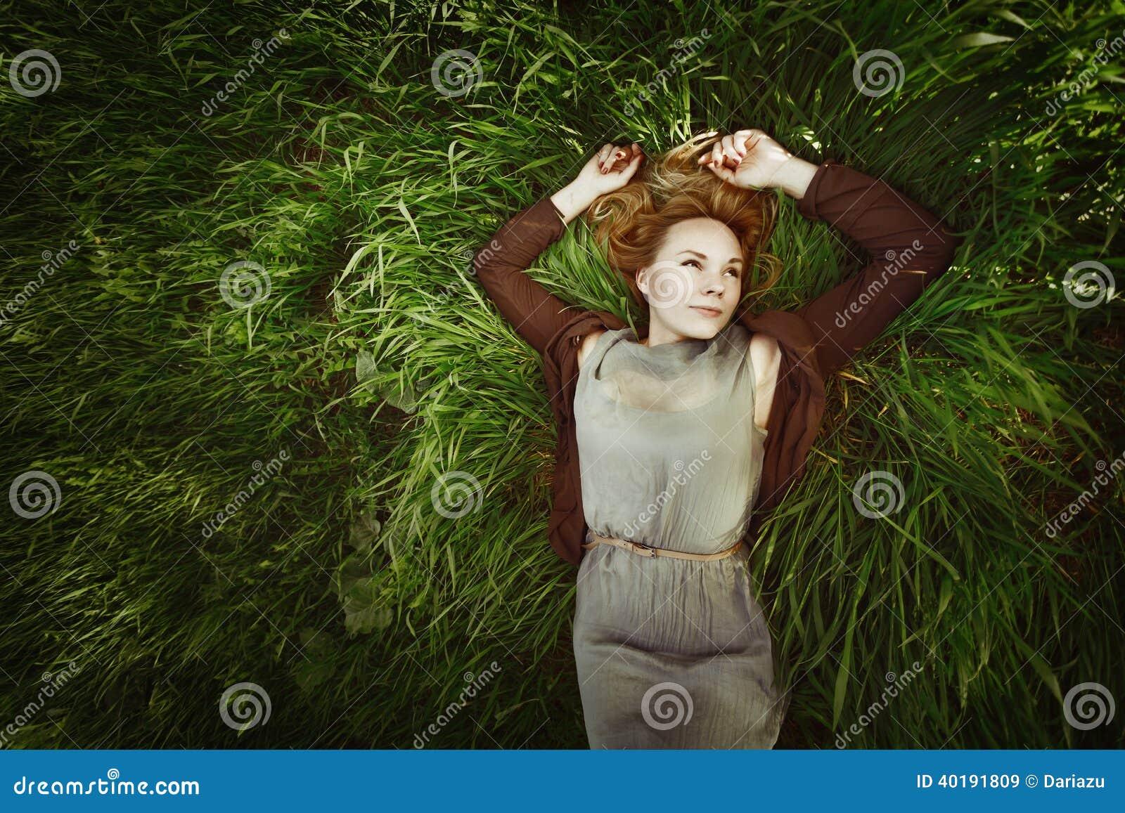 Härlig ung kvinna som ligger i gräset. Retro färger. Sommar,