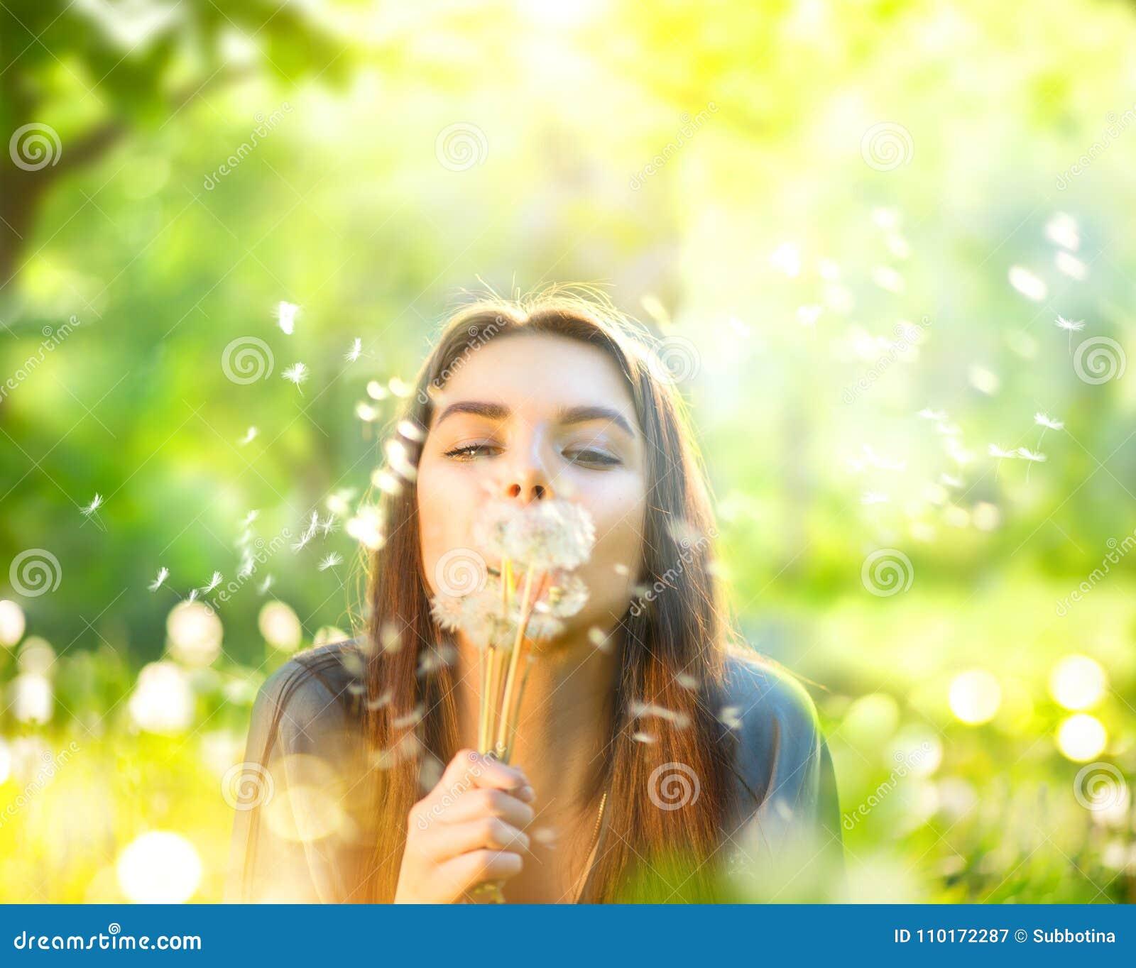 Härlig ung kvinna som ligger på grönt gräs och blåser maskrosor