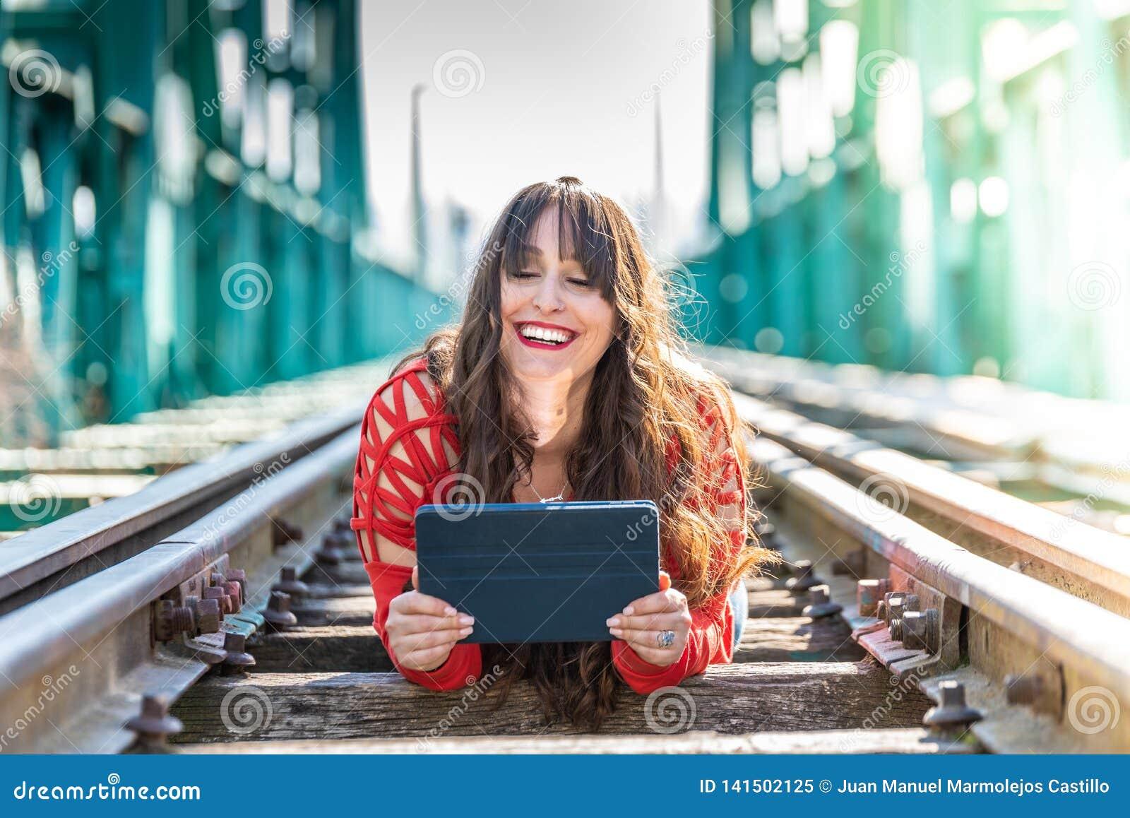 Härlig ung kvinna som ner ligger på drevspår genom att använda den Digital minnestavlan