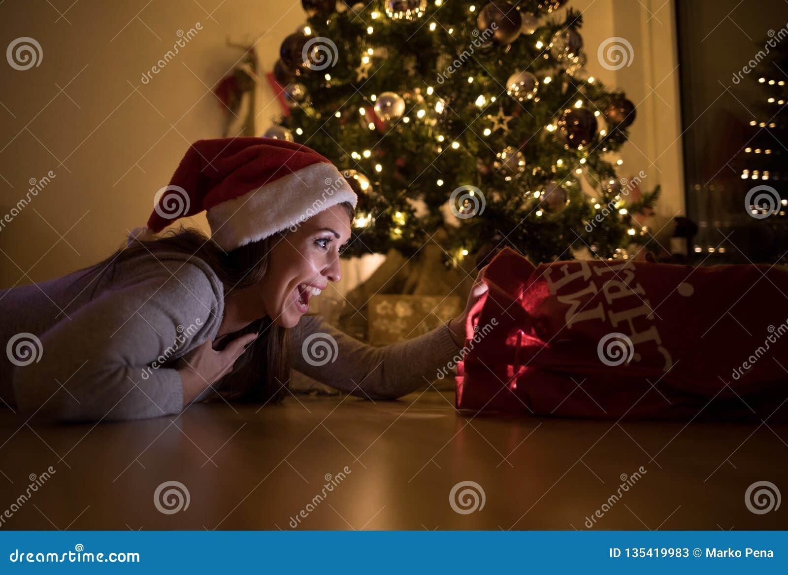 Härlig ung kvinna som ser förvånad på hennes julgåva