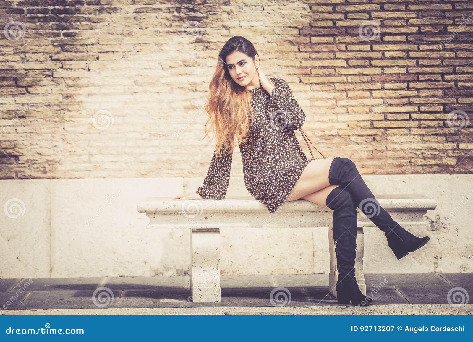 Härlig ung kvinna som sitter utomhus på en bänk Trendigt och sinnligt