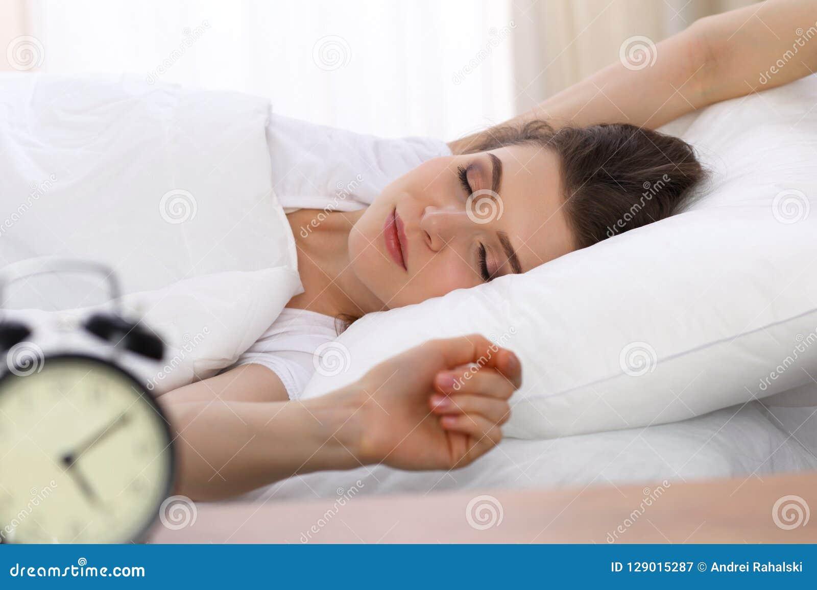 Härlig ung kvinna som sover, medan ligga i hennes säng Begreppet av angenämt och vilar återinsättandet för aktivt liv