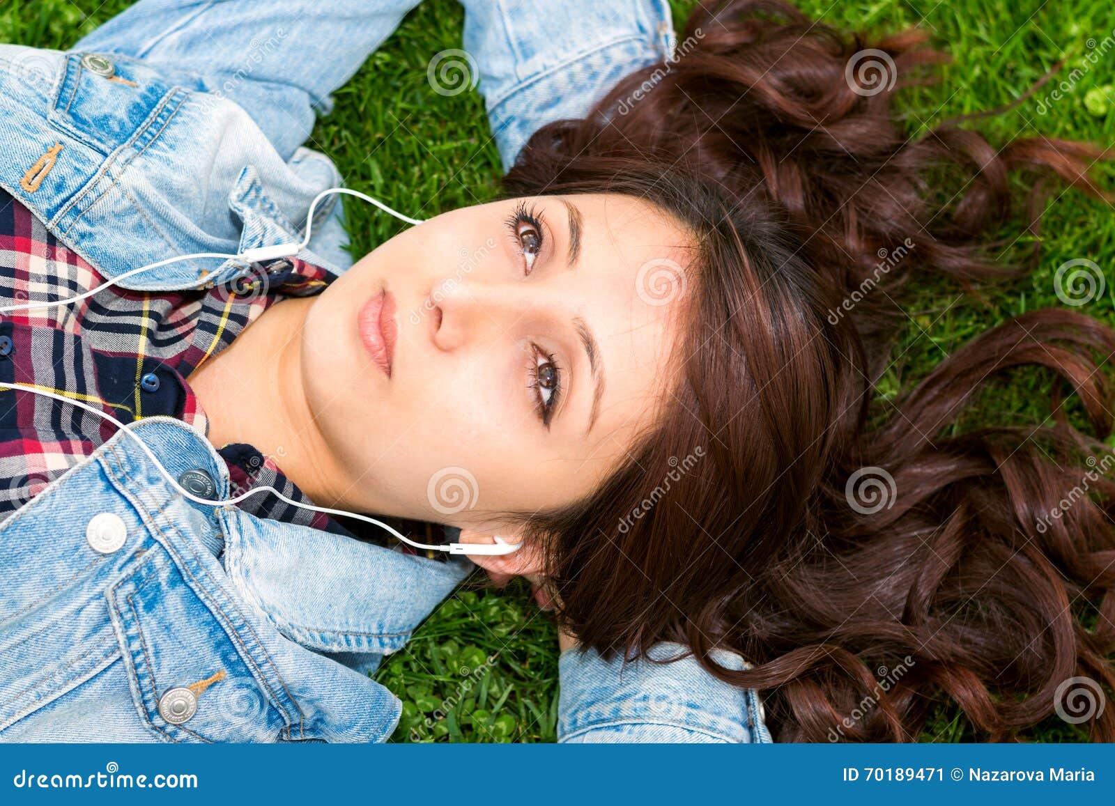 Härlig ung kvinna som vilar på gräset