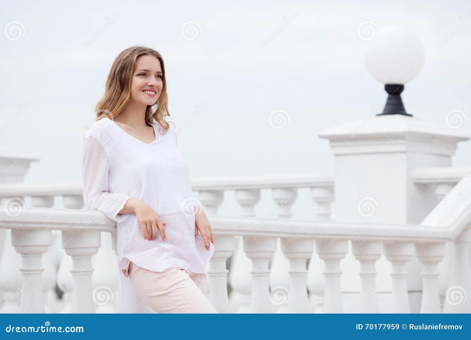 Härlig ung le kvinna på stads- bakgrund