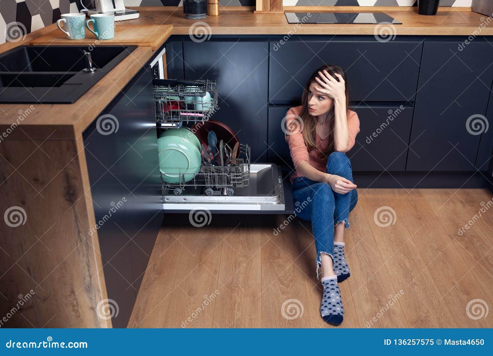 Härlig ung le kvinna som gör disk i köket