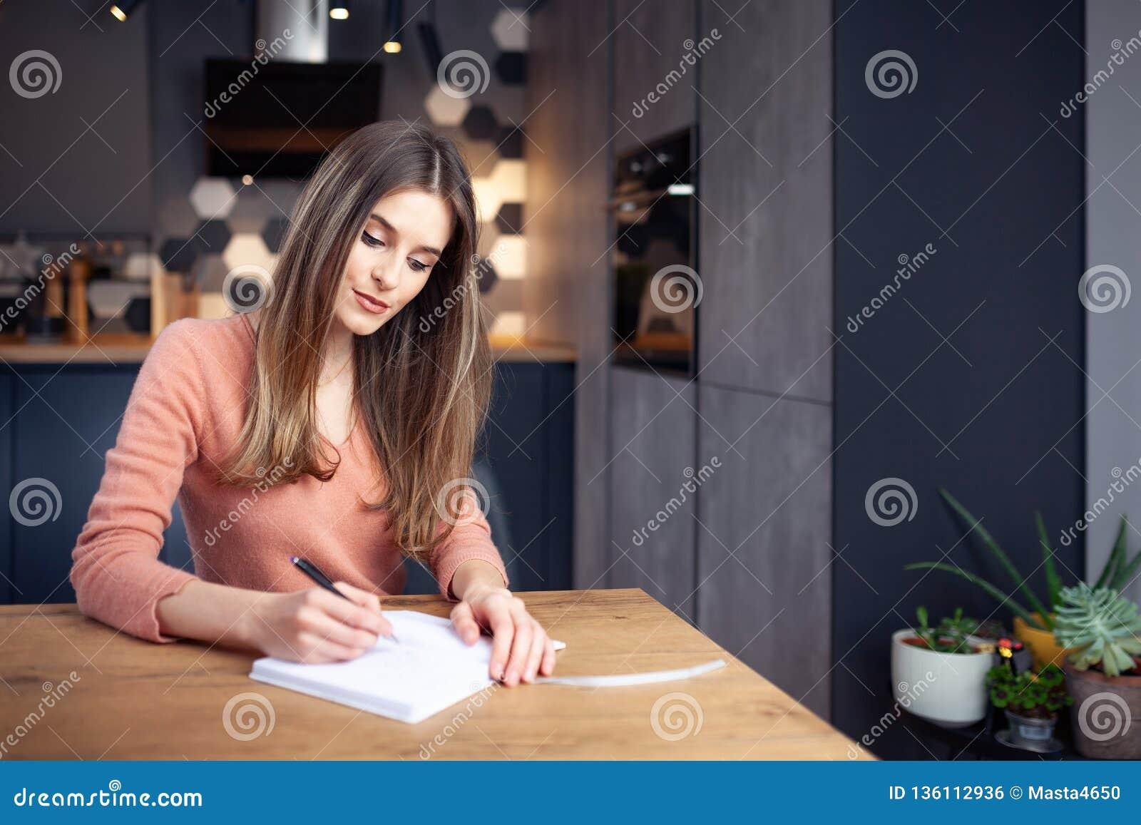 Härlig ung le kvinna som hemifrån arbetar
