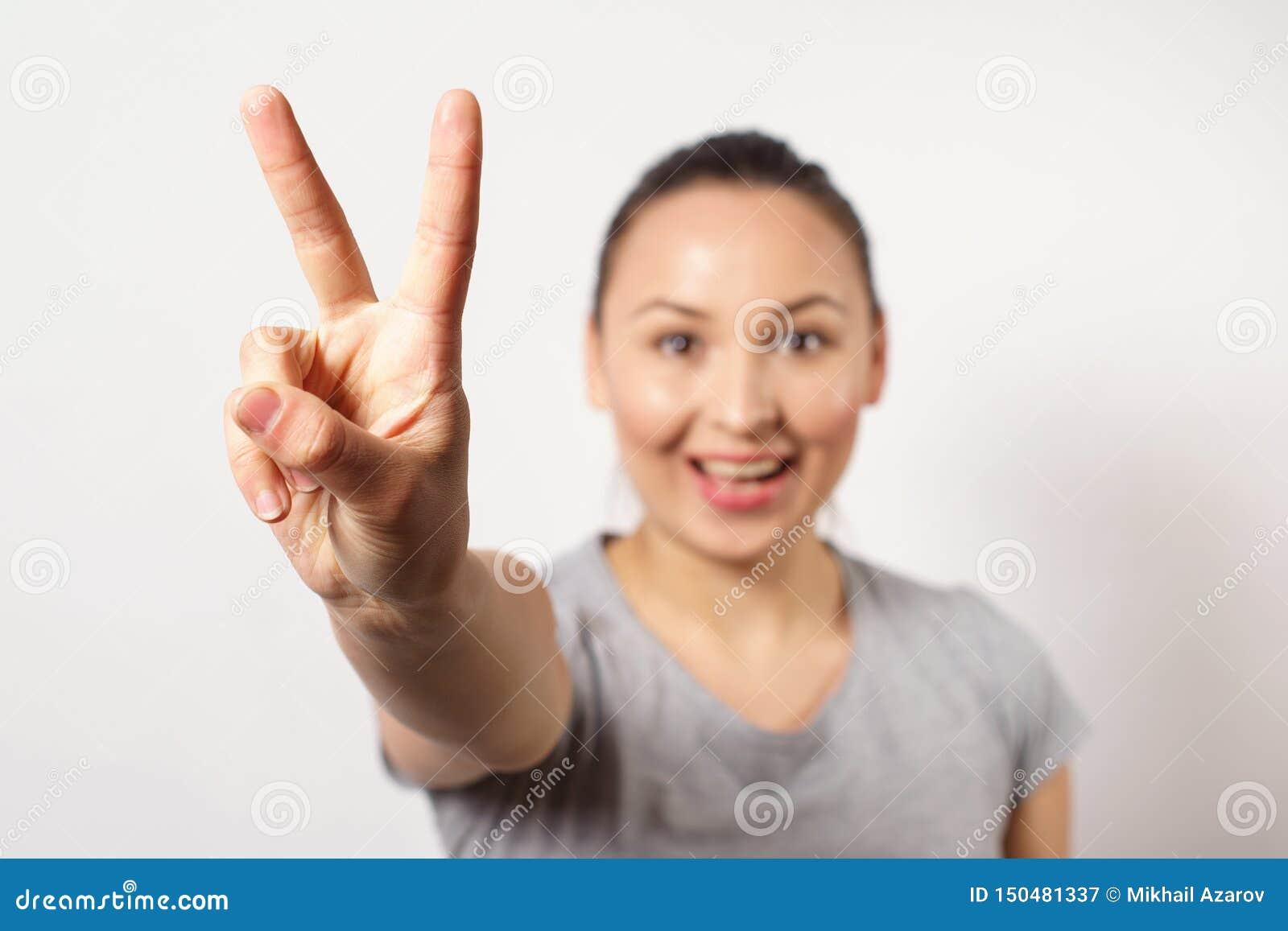 Härlig ung lycklig le victopy flickauppvisning sjunger med hennes hand Fredbegrepp Tecken av gester