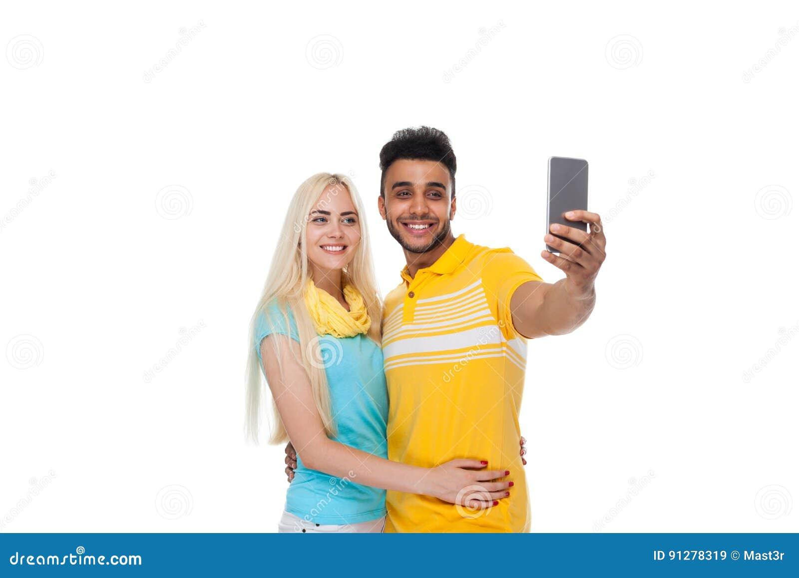 Härlig ung lycklig parförälskelse som ler att omfamna ta det Selfie fotoet på den cellSmart telefonen, latinamerikansk mankvinna