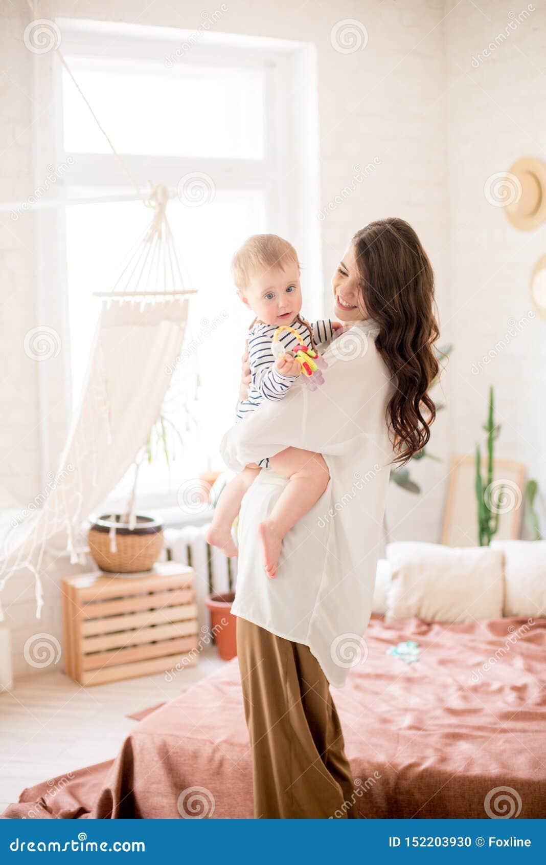Härlig ung moder med långt mörkt hår i enkla bekväma kläderlekar med hennes unga son i ett hemtrevligt sovrum