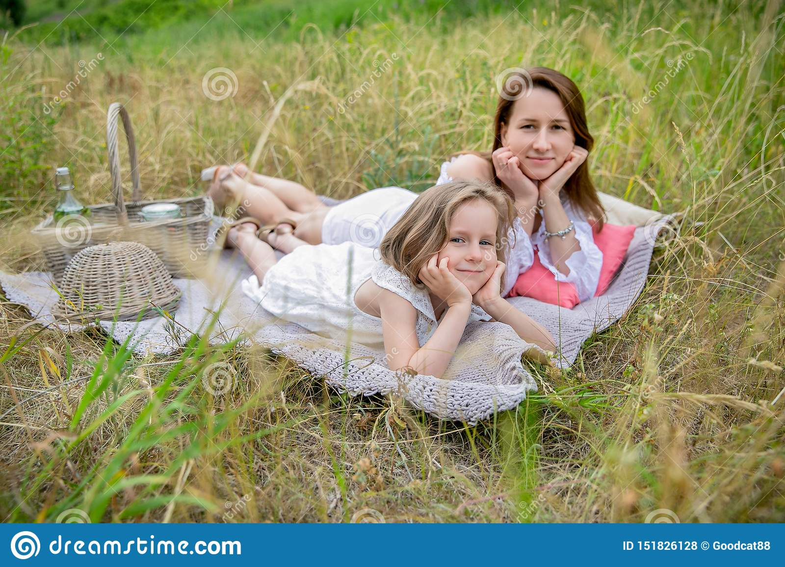 Härlig ung moder och hennes lilla dotter i den vita klänningen som har gyckel i en picknick De ligger på en pläd på gräset och