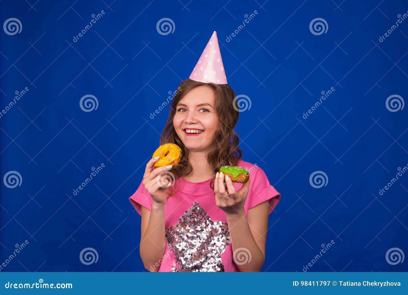 Härlig ung rolig flicka med donuts på blå bakgrund Sjukligt banta, skräpmat-, parti- och berömbegreppet