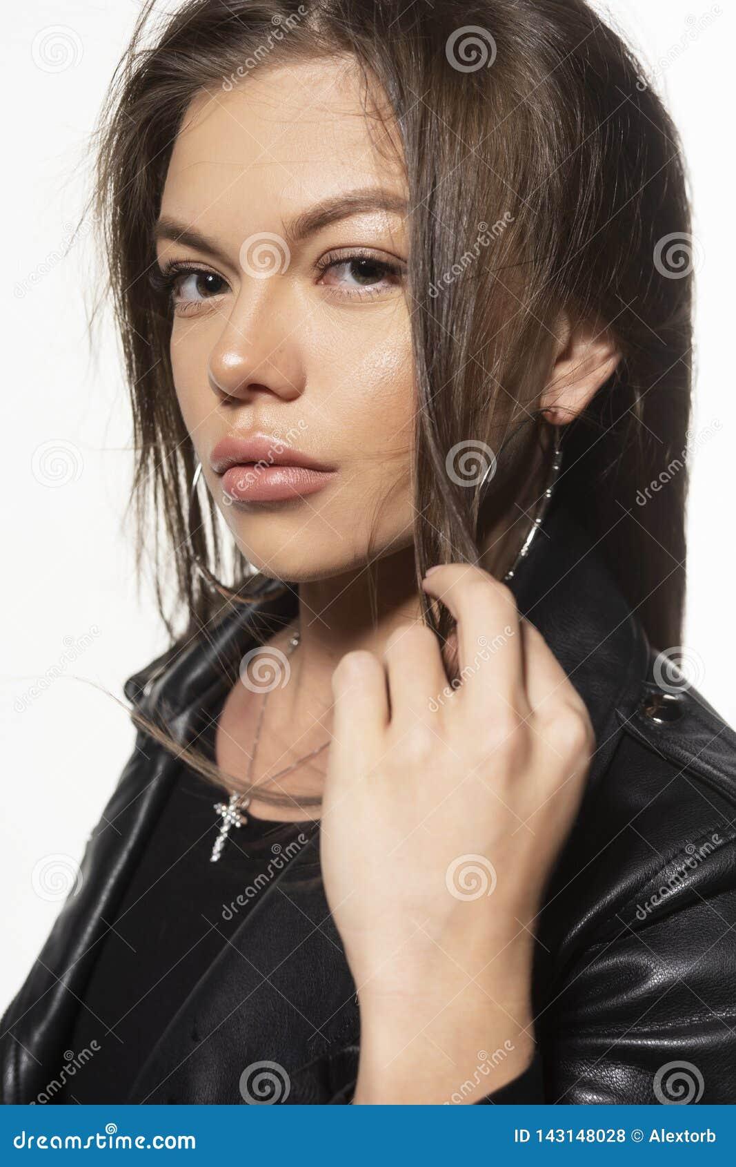 Härlig ung sexig cyklistflicka som bär en bodysuit och örhängen för svartläderomslag bakgrund isolerad white kommersiellt