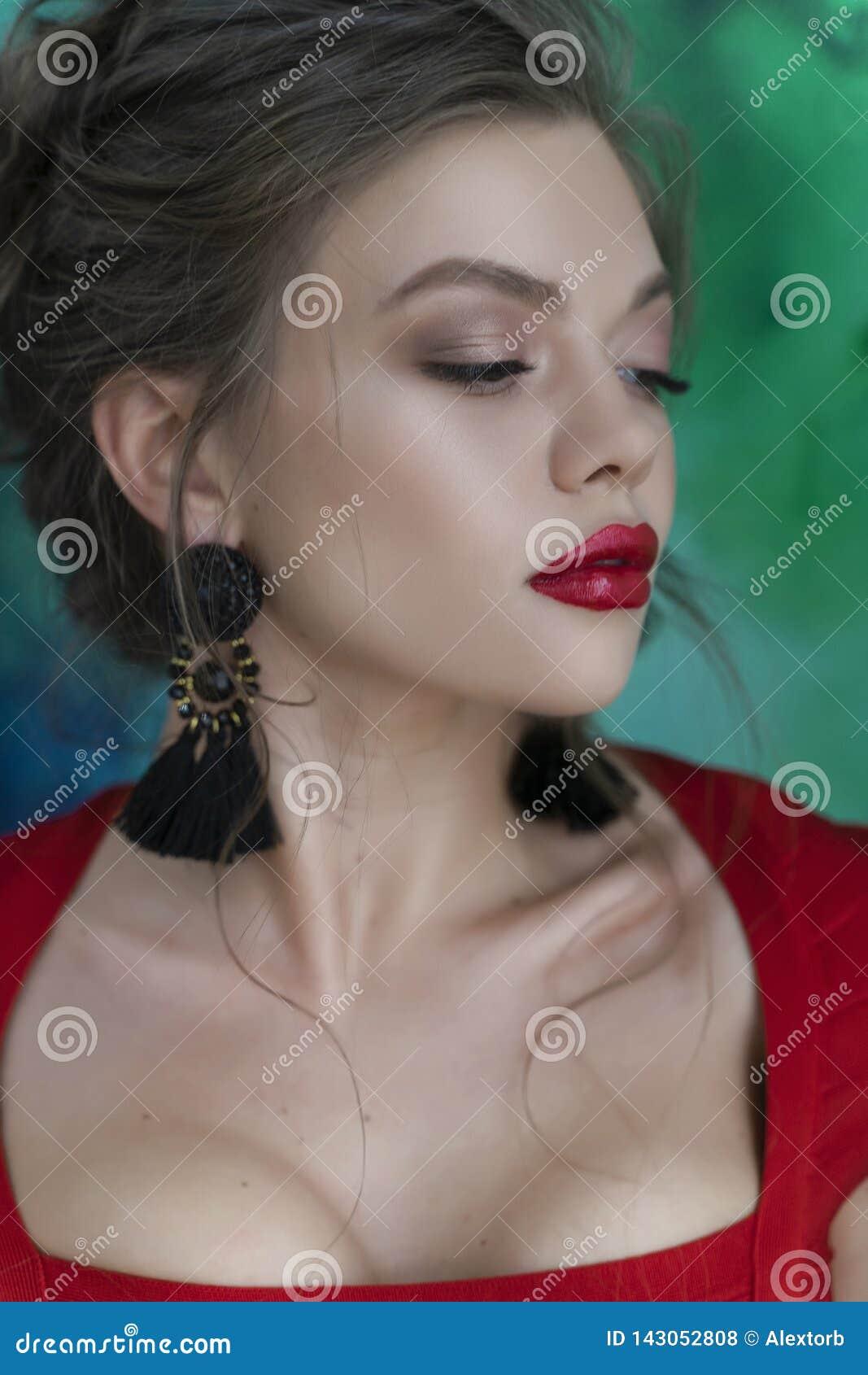 Härlig ung sexig elegant flicka med stora bröst och att bära en röd åtsittande klänning och örhängen som står sensually på en grä