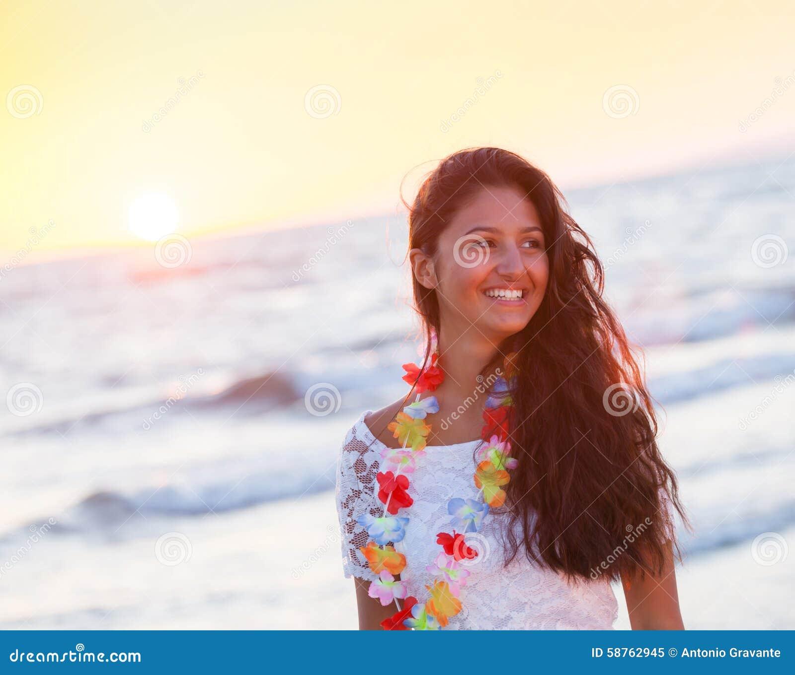 Härlig ung tonåring med en vit klänning på stranden på solar
