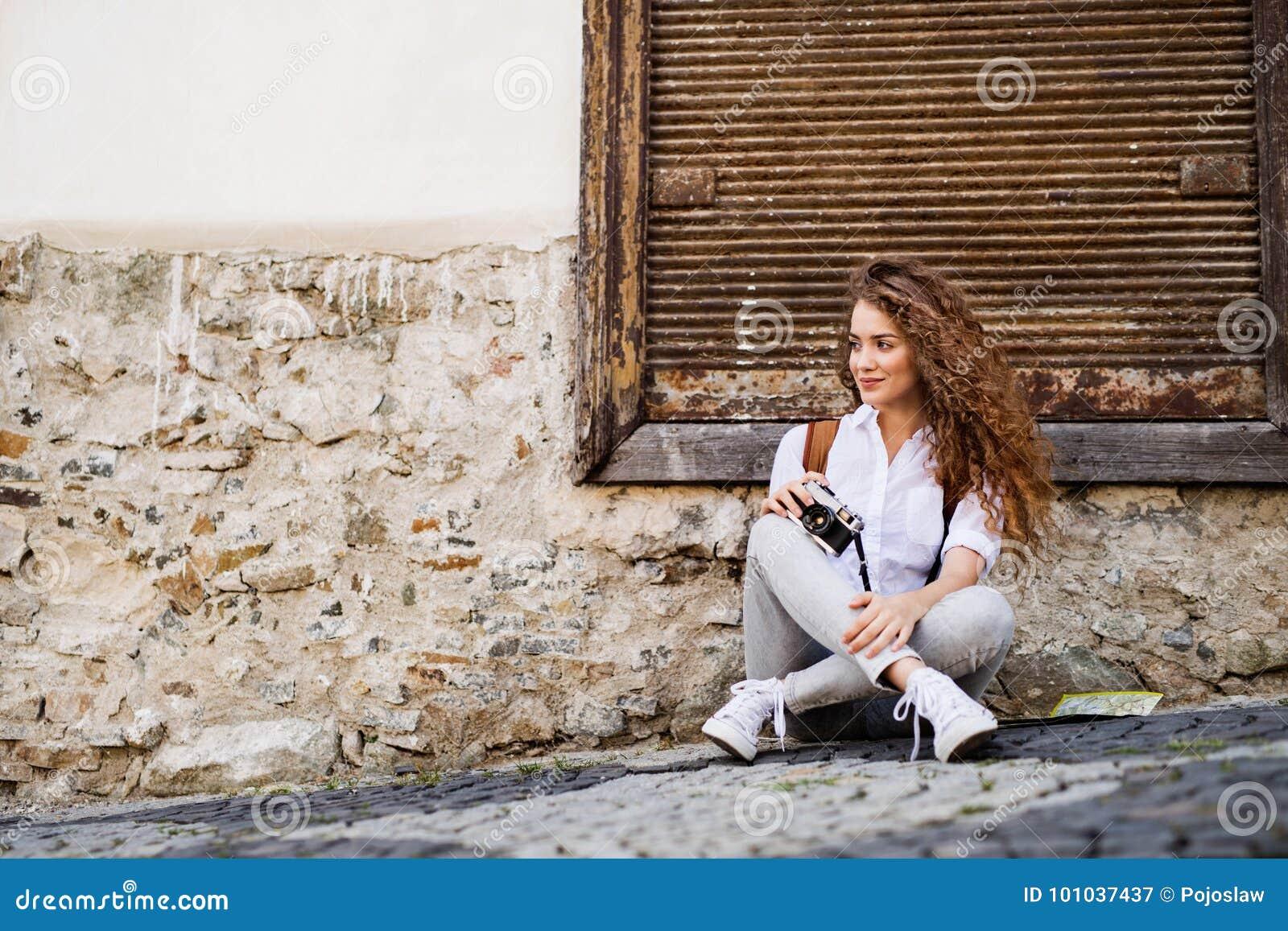 Härlig ung turist med kameran i den gamla staden