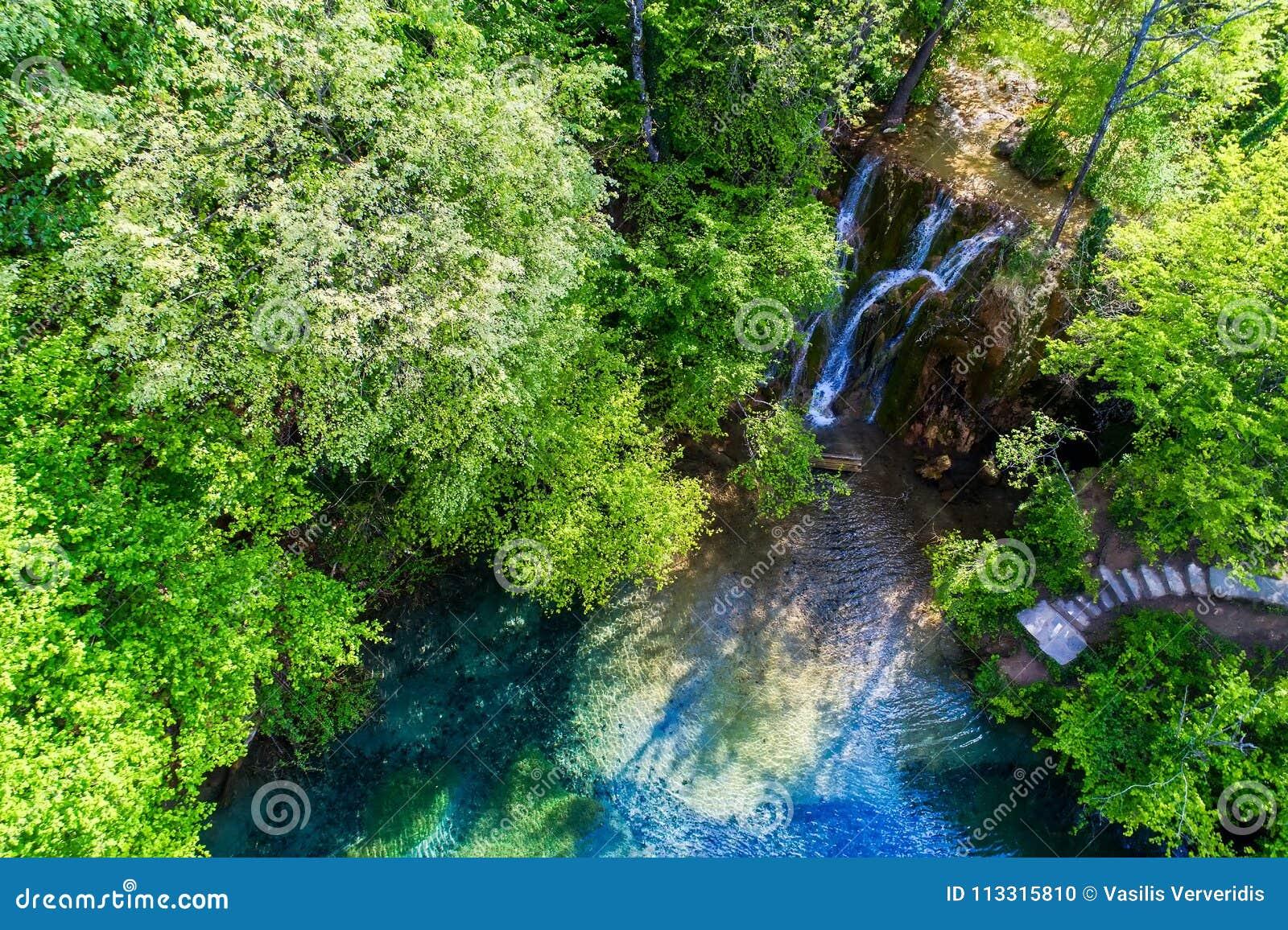 Härlig vattenfall och en liten sjö med gräsplanvatten i Skra a