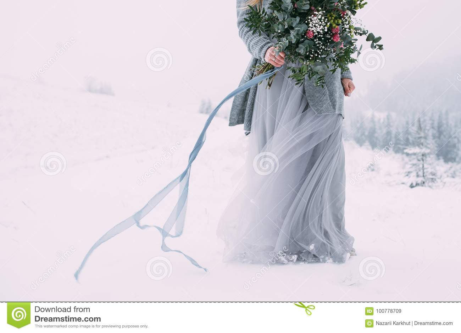 Härlig vinterstående av den unga kvinnan i det snöig landskapet för vinter