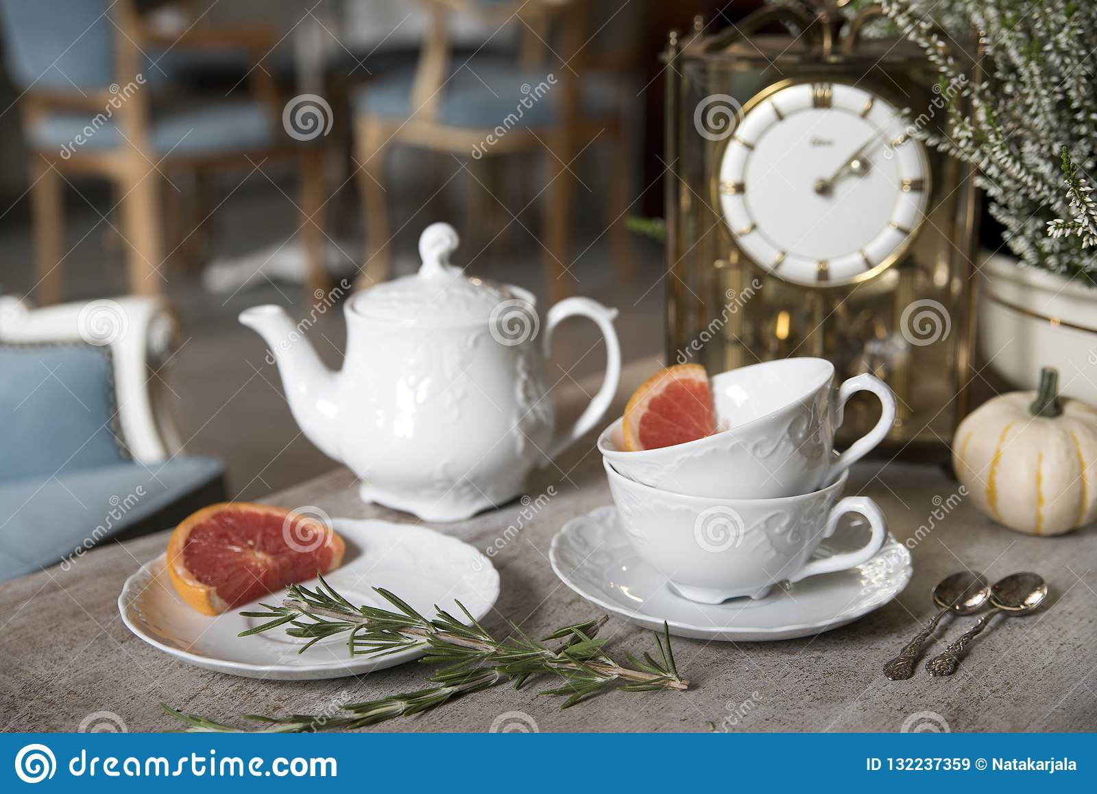 Härlig vit tekanna, koppar och tefat, antik klocka, pumpa, ljung, rosmarin och grapefrukt 1 livstid fortfarande