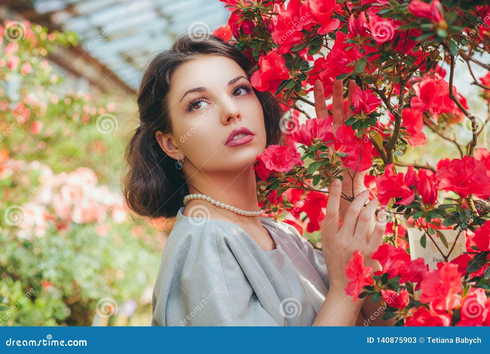 Härlig vuxen flicka i ett azaleaväxthus som drömmer i en härlig retro klänning och hatt