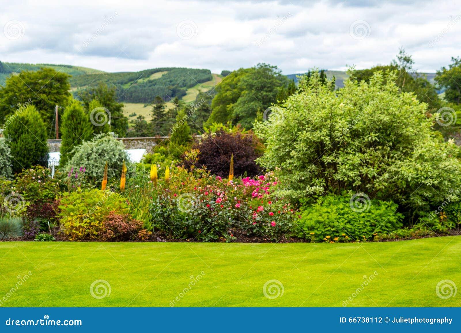 Härlig walled, victorianträdgård med variation av blommor och träd
