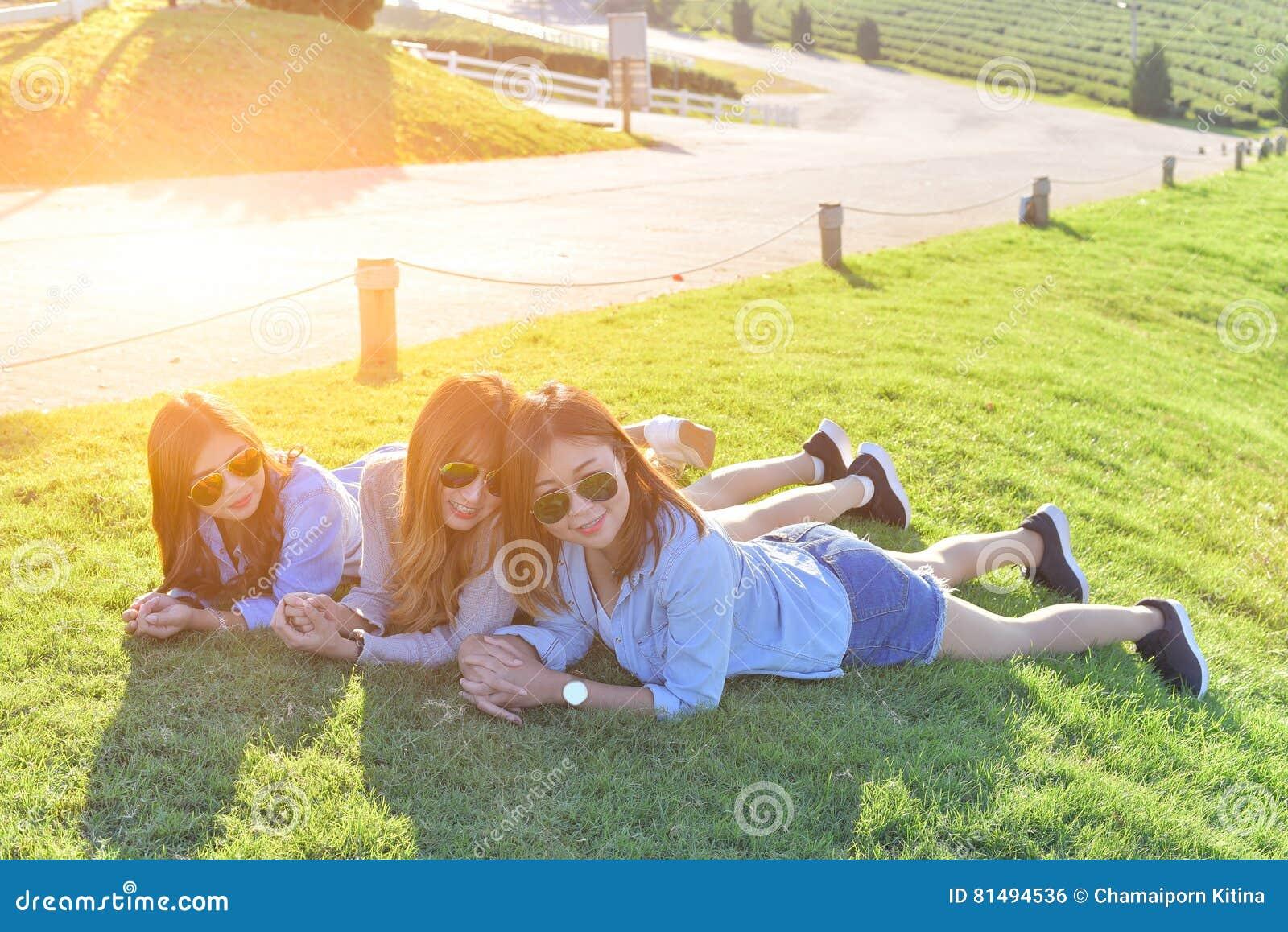 Härliga asiatiska flickor som lägger på det gröna gräset under solljus, w