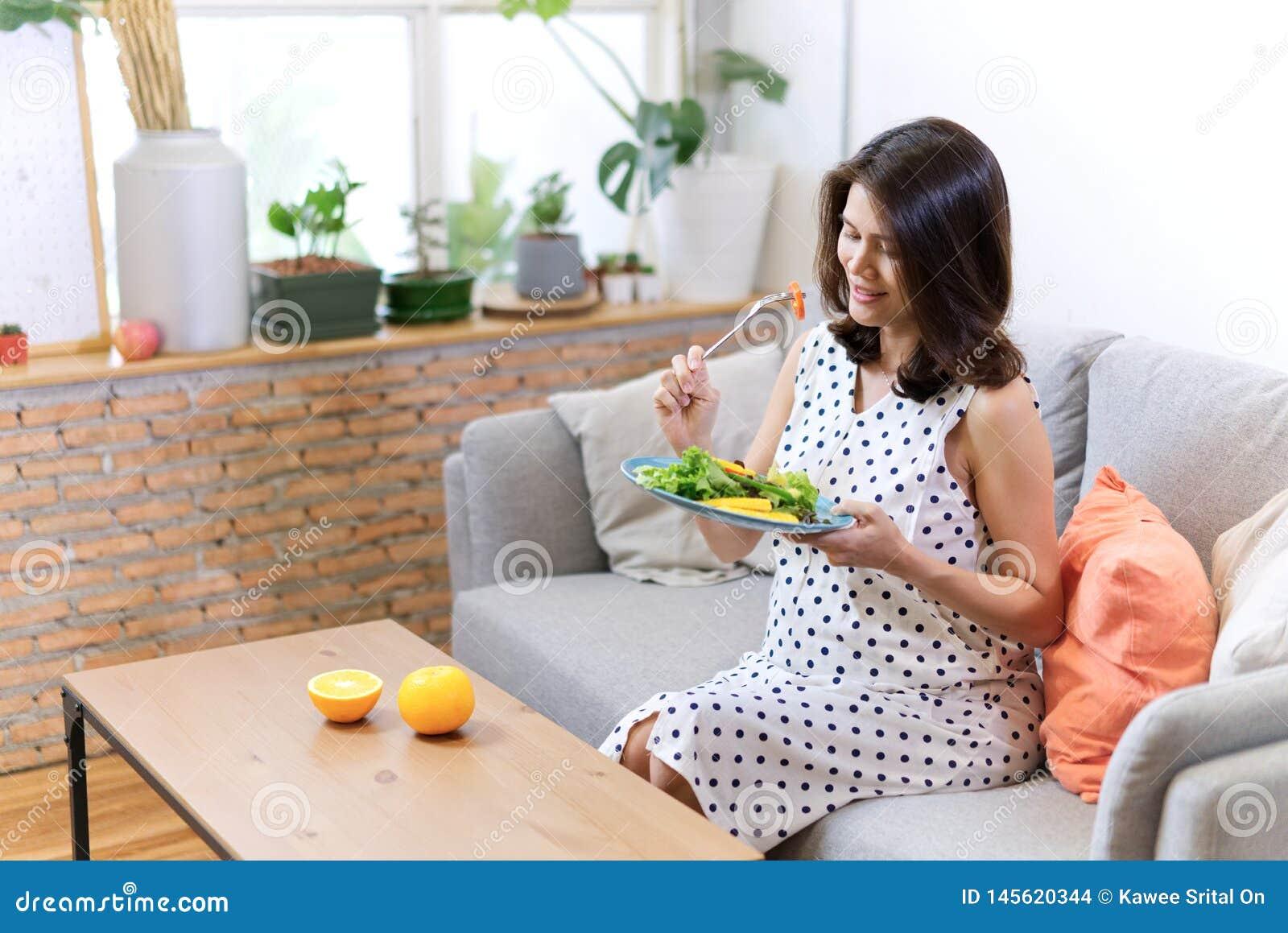 Härliga asiatiska gravida kvinnor som sitter på soffan, har sallad för hennes frukost som några apelsiner är pålagda tabellen Hav
