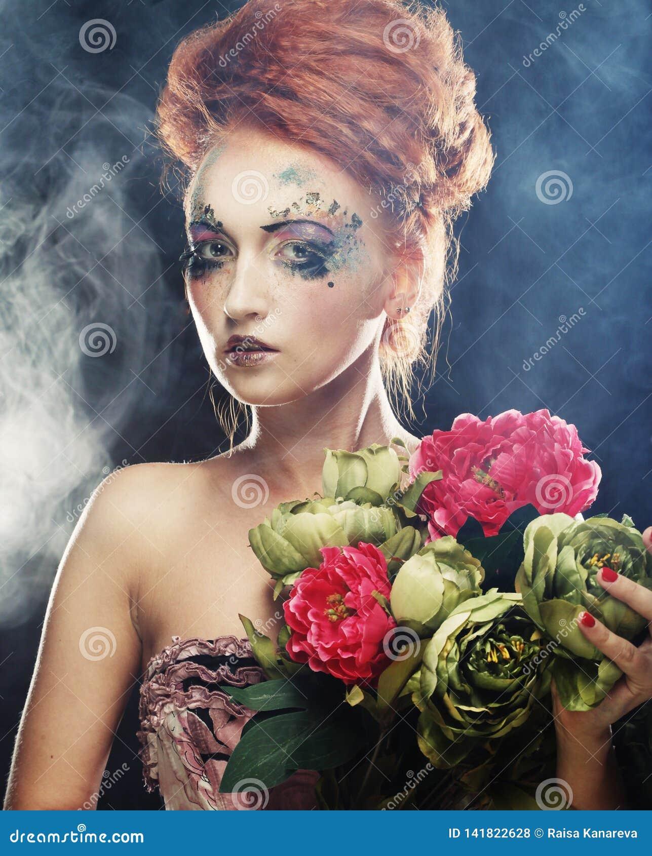 Härliga blommor för redhairkvinnainnehav