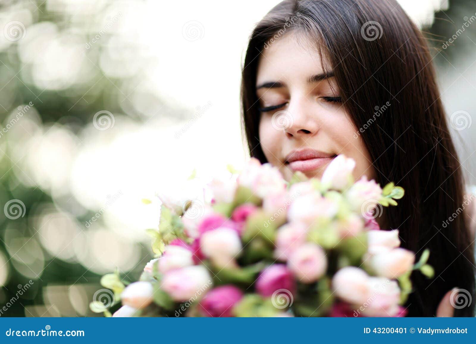 Download Härliga Blommor Som Luktar Kvinnan Fotografering för Bildbyråer - Bild av nätt, blommor: 43200401