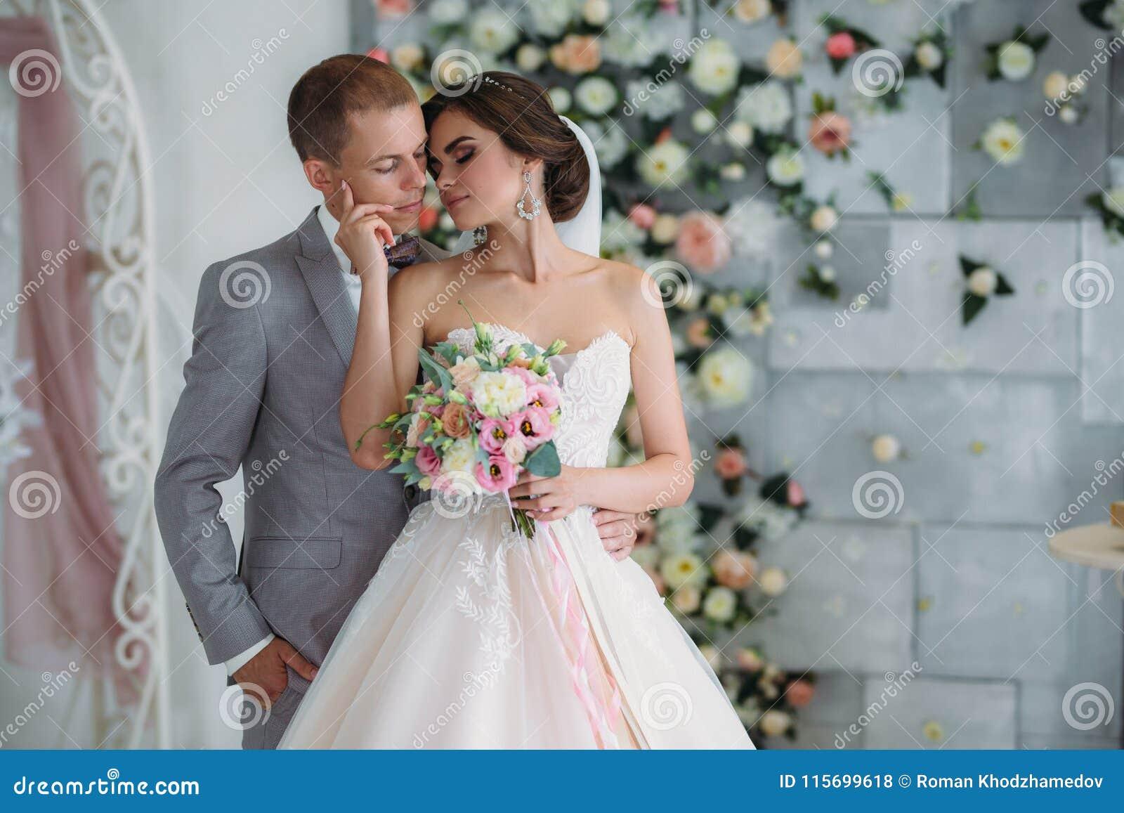 6e9eaf1997a2 Härliga brölloppar som kramar i ljus studio Brudgummen i en affärsgrå färg  passar, en vit skjorta i en fluga och en knapphål, en brud i en lyxig  klänning ...
