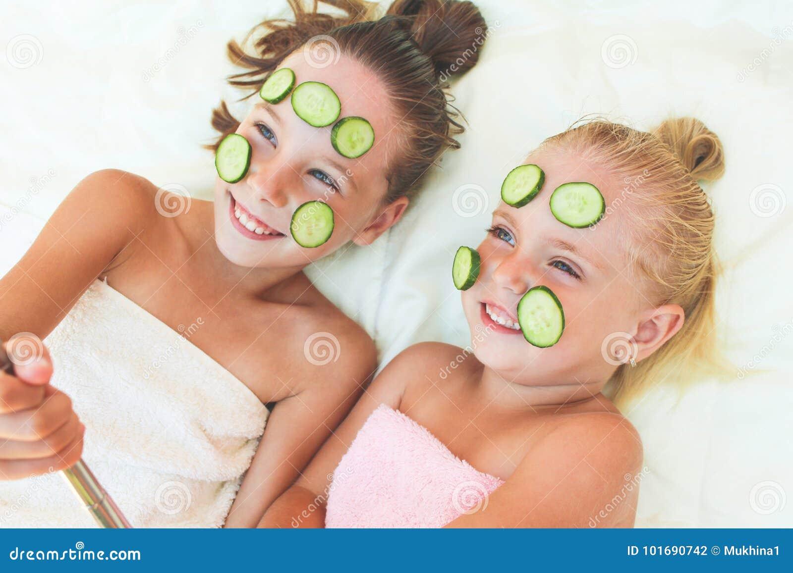 Härliga flickor med den ansikts- maskeringen av gurkan