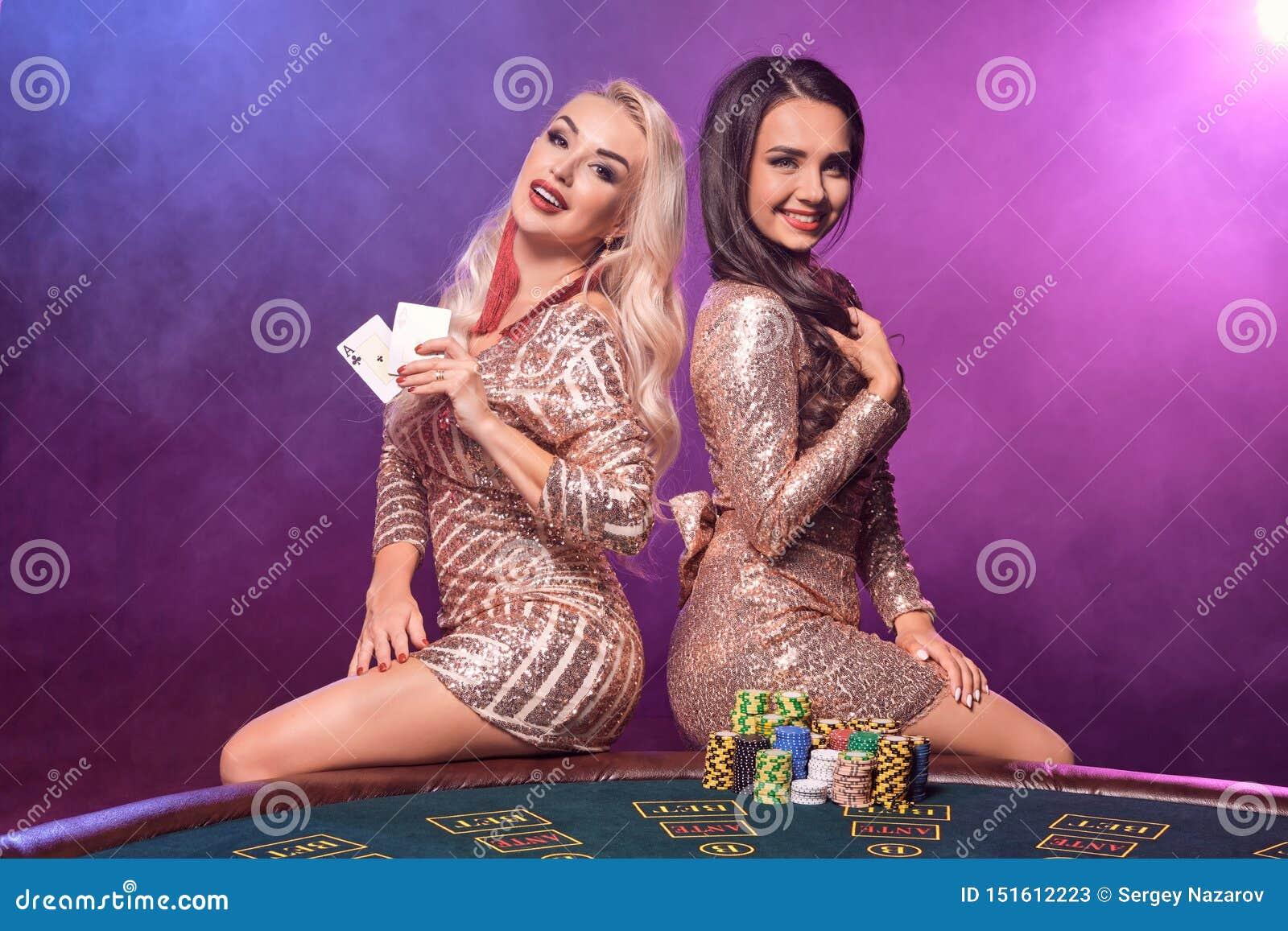 Härliga flickor med perfekta frisyrer och det ljusa sminket poserar anseende på en spela tabell Kasino poker