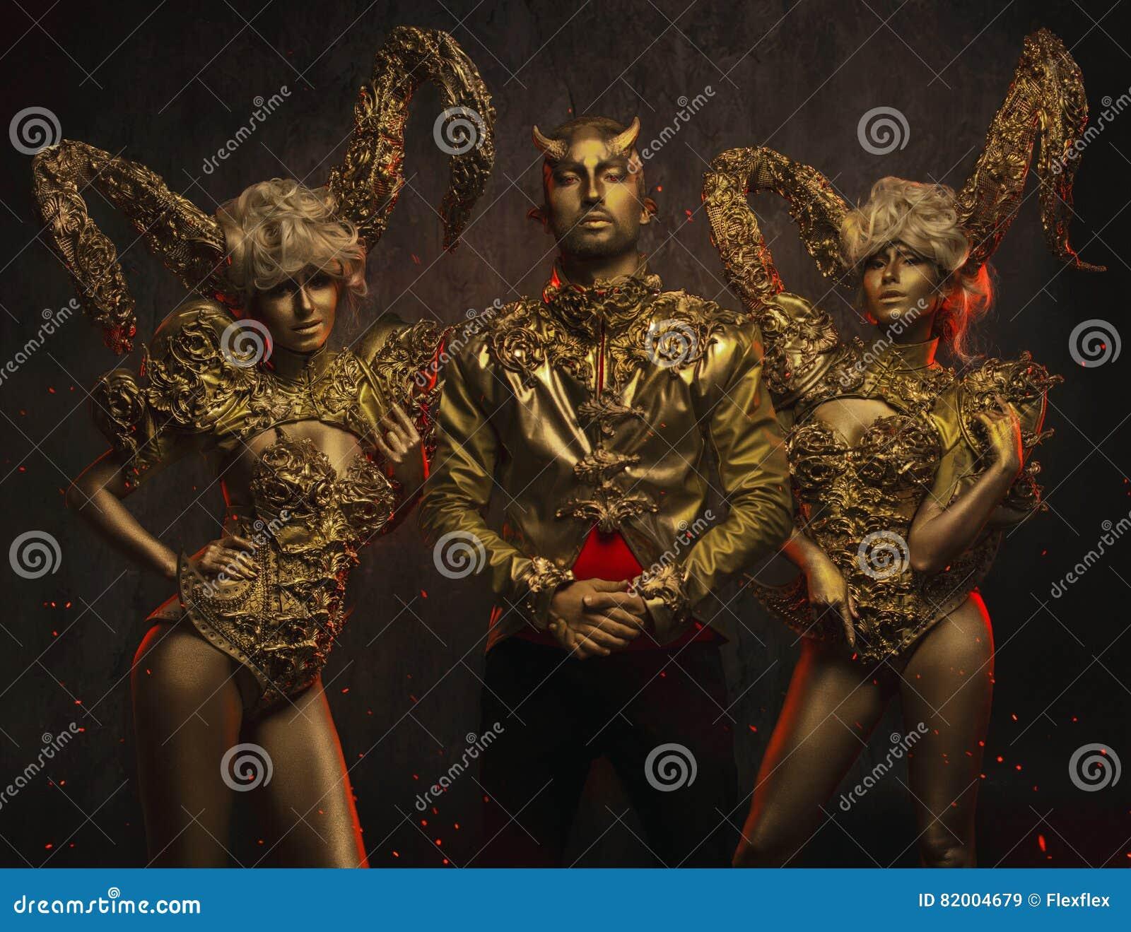 Härliga jäkelkvinnor med guld- dekorativa horn och den stiliga jäkelmannen i dekorativt omslag