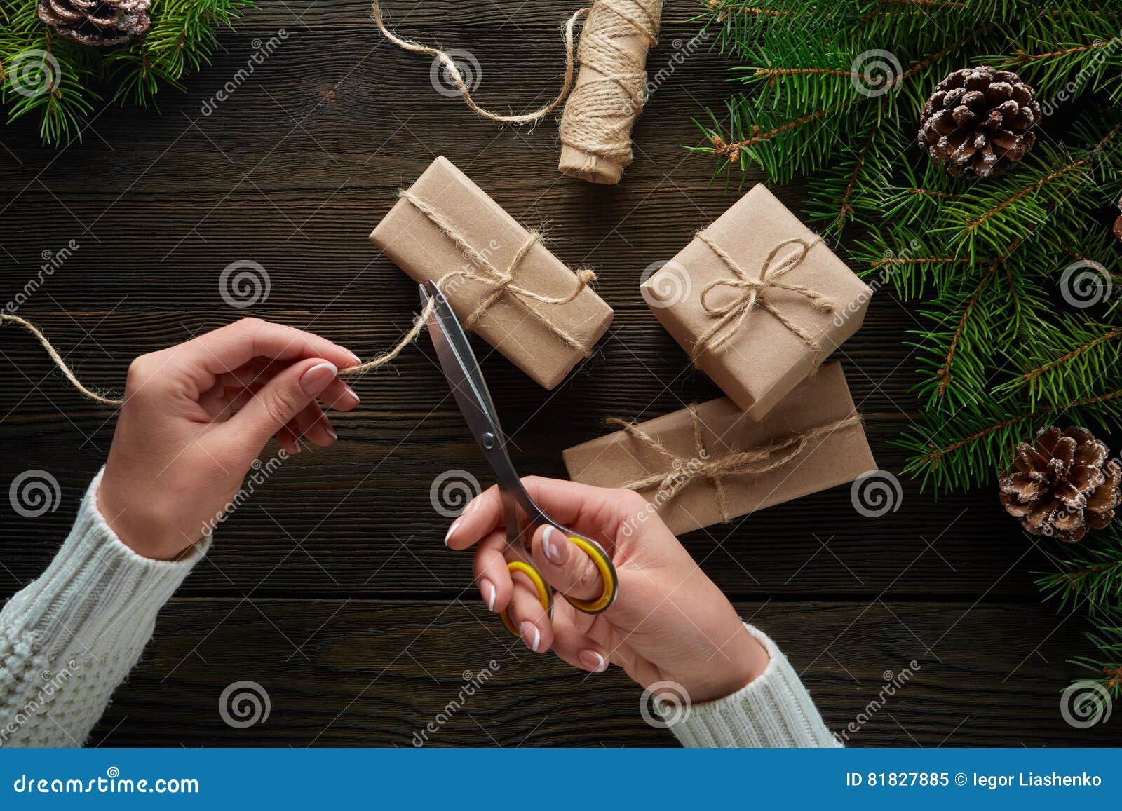 Härliga kvinnlighänder med sax som klipps av repet, julgåvor i brunt kraft papper