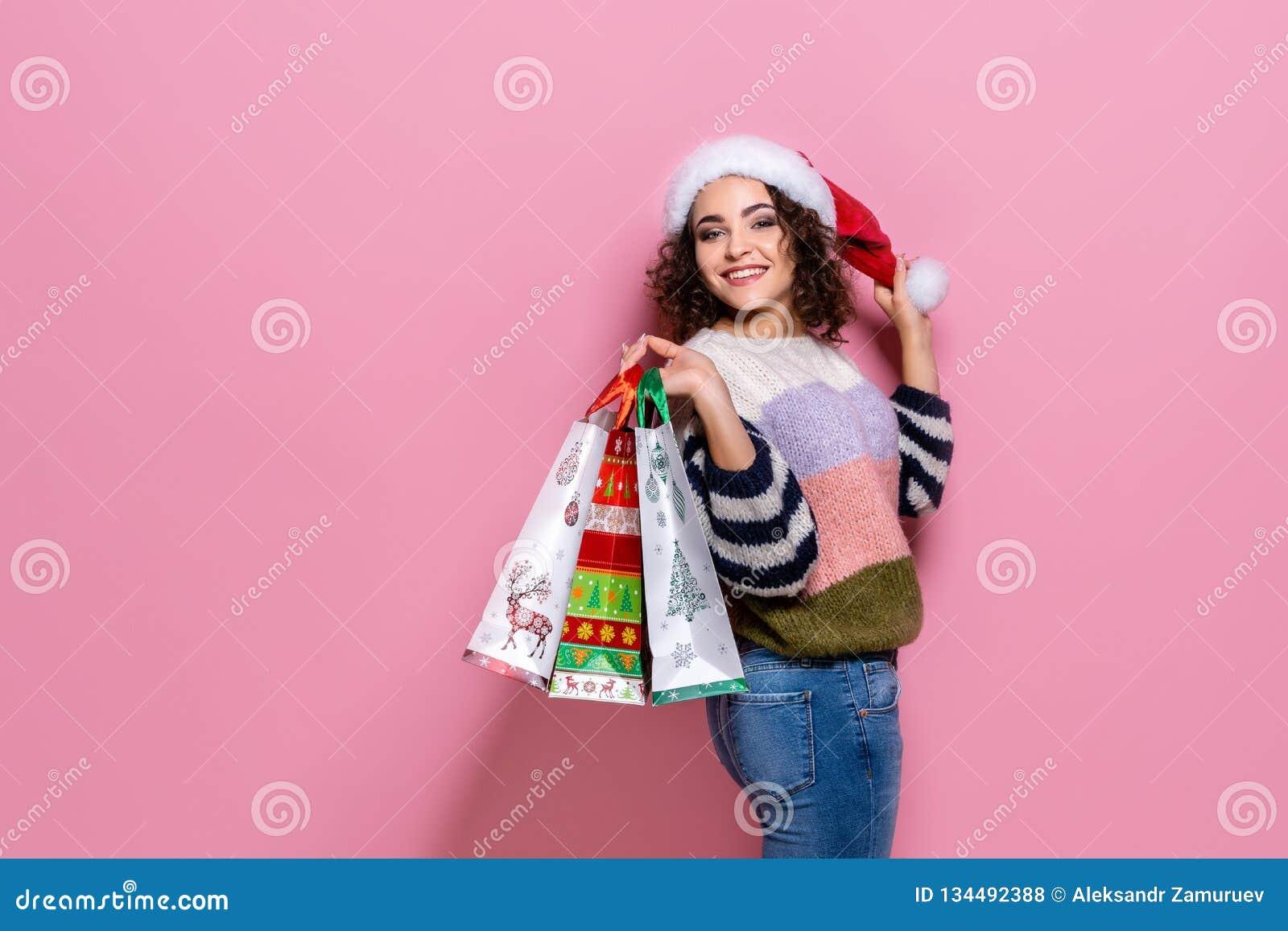 Härliga kvinnor som bär ljus jul som bär färgrika shoppa påsar På rosa bakgrund Julshopping och