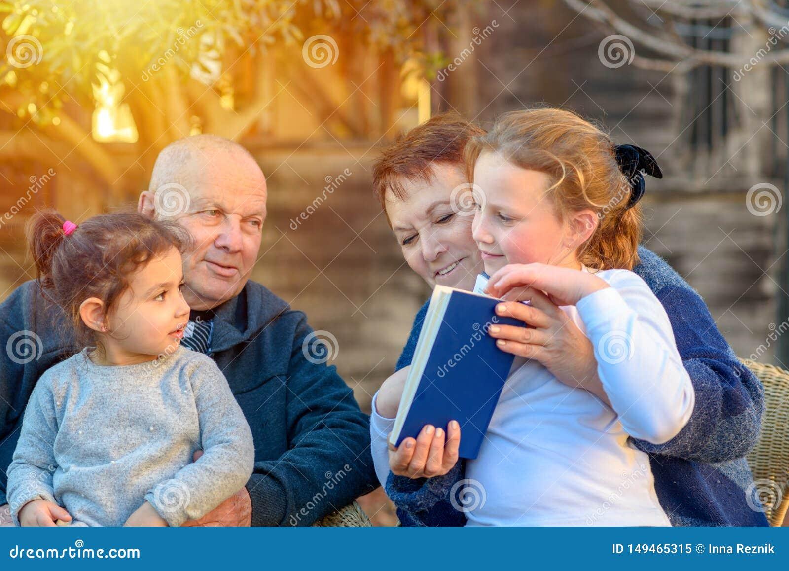 Härliga lyckliga gamla par och sondöttrar som tillsammans läser en bok i naturen på solnedgången