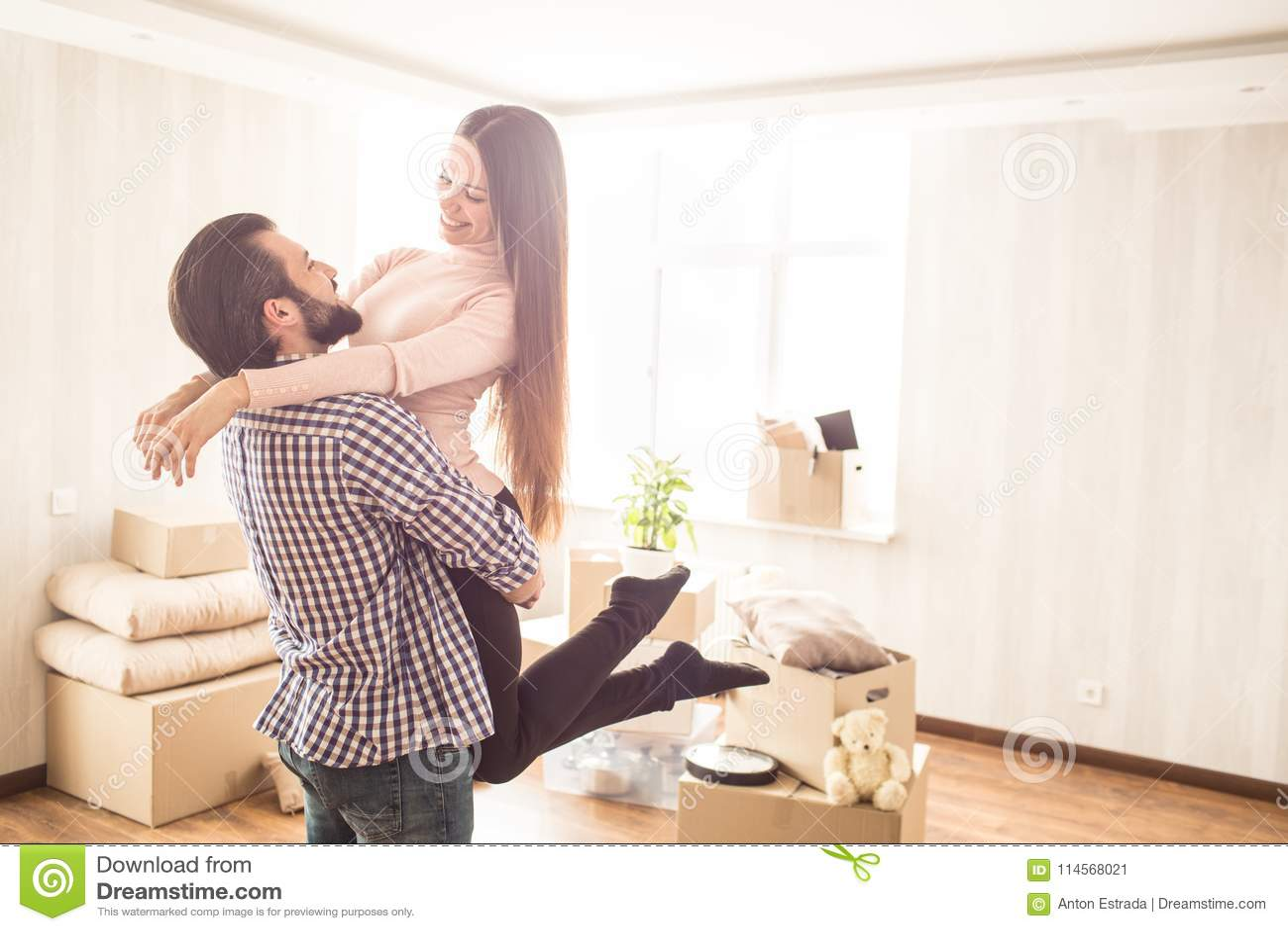 Härliga par står i ett ljust rum med packade upp askar Den unga mannen rymmer hans attraktiva fru i händer