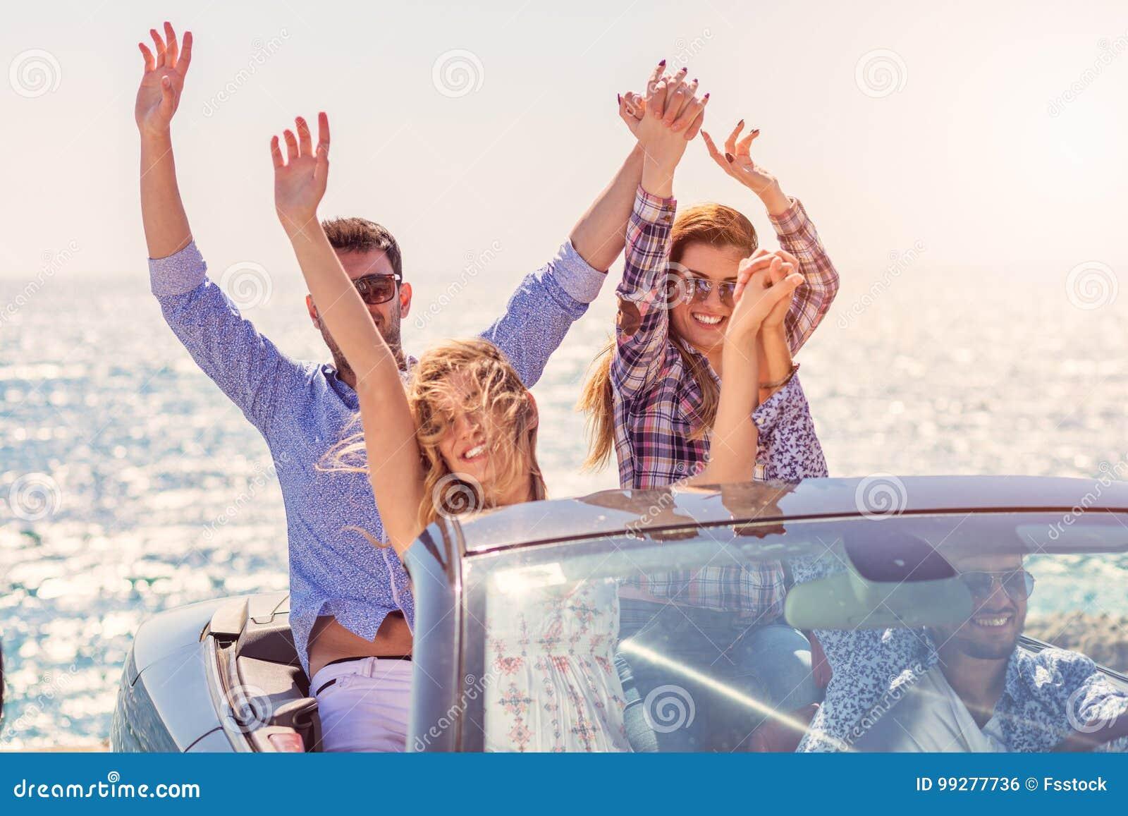 Härliga partivänflickor som dansar i en bil på den lyckliga stranden