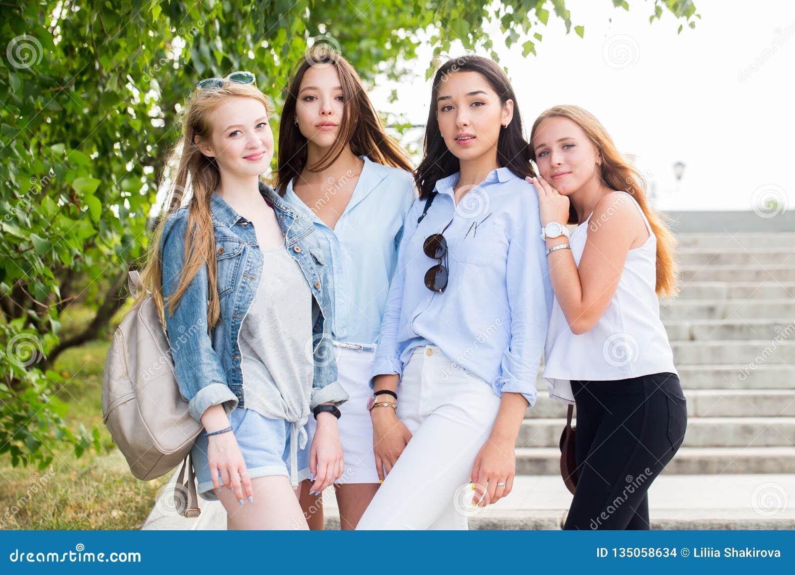 Härliga roliga fyra flickvänner jublar och ler på kameran i parkera i sommaren