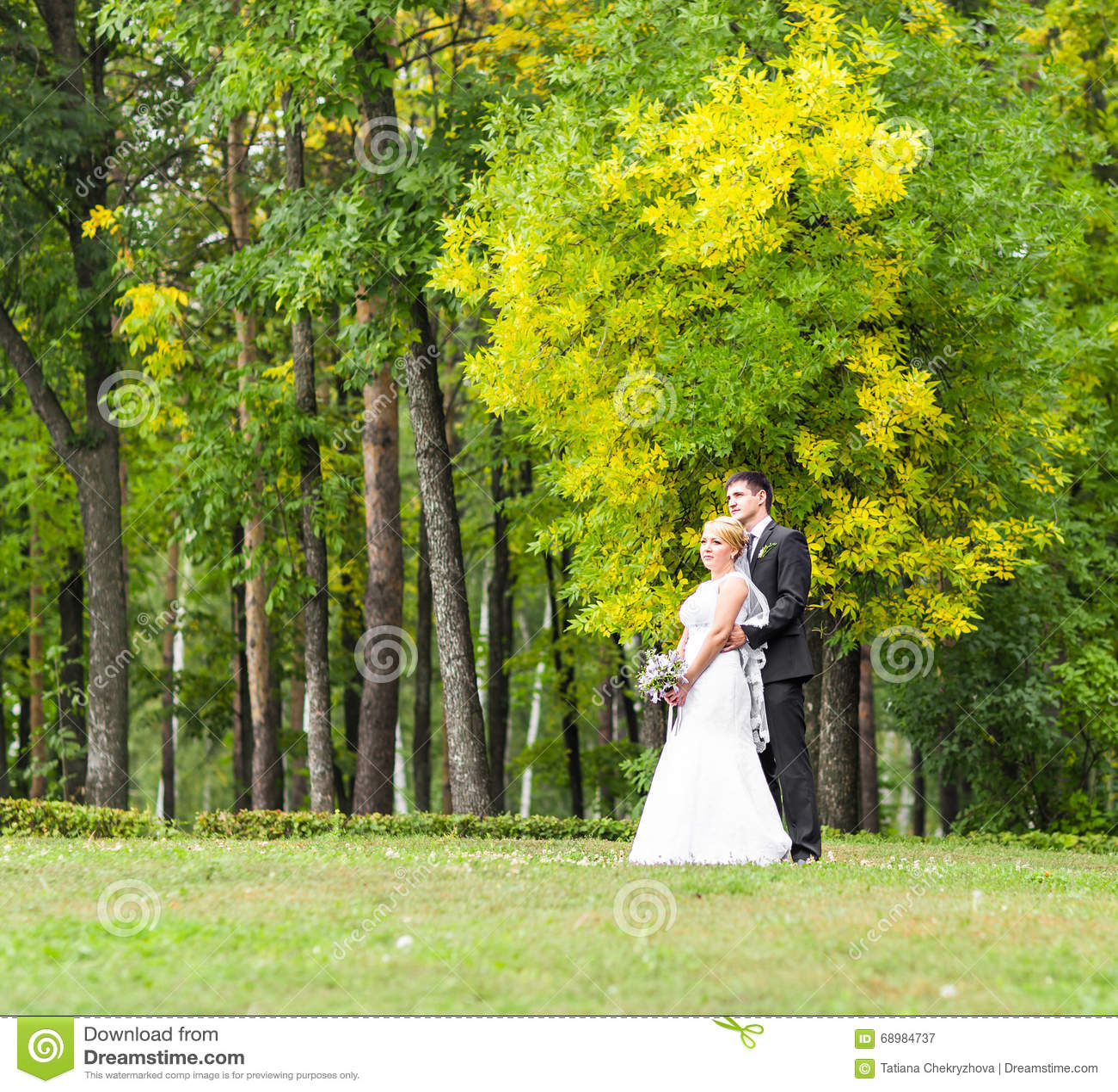 Härliga romantiska brölloppar som utomhus kysser och omfamnar