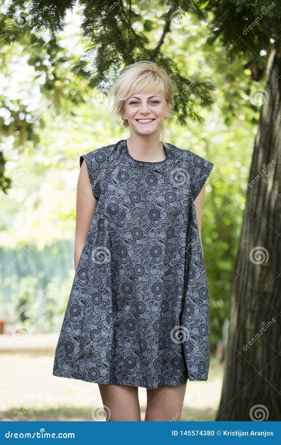 Härliga unga kvinnor som ler, medan stå under sörja trädet i trevlig klänning