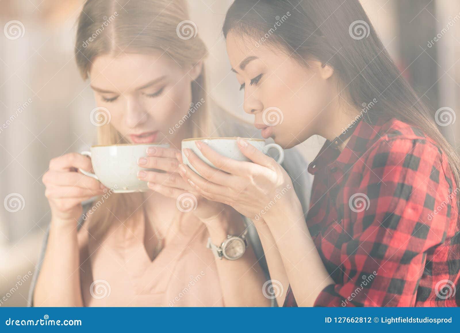 Härliga unga kvinnor som rymmer vita koppar och dricker nytt kaffekaffe