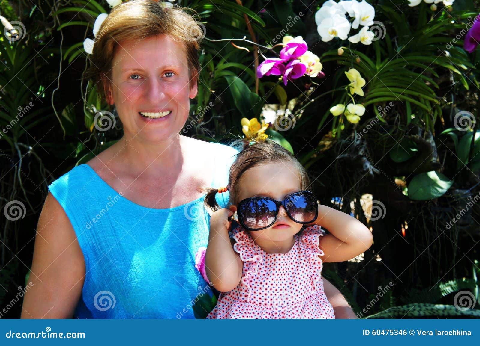 Härligt behandla som ett barn sammanträde på varven av en kvinna i bakgrundsorkidérna Skratta för kvinna behandla som ett barn at