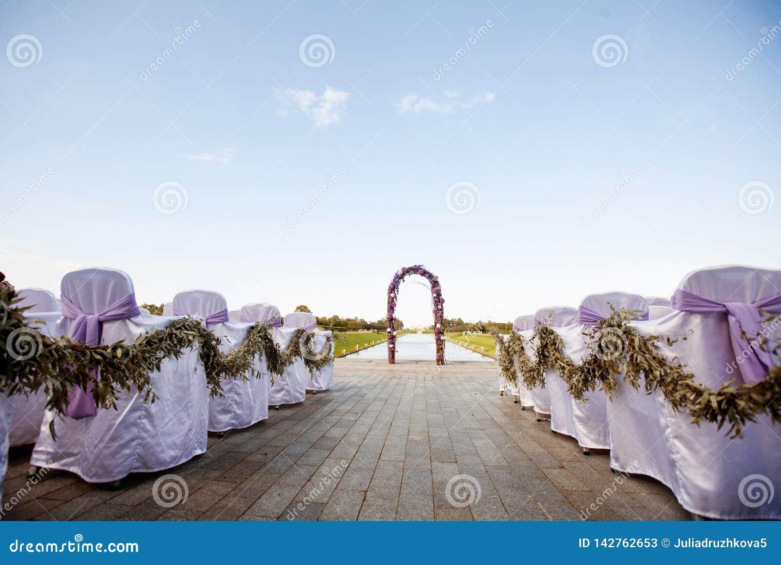Härligt bröllop Den runda bågen dekoreras med blommor och grönska, ceremonin på kusten Gäststolar dekoreras