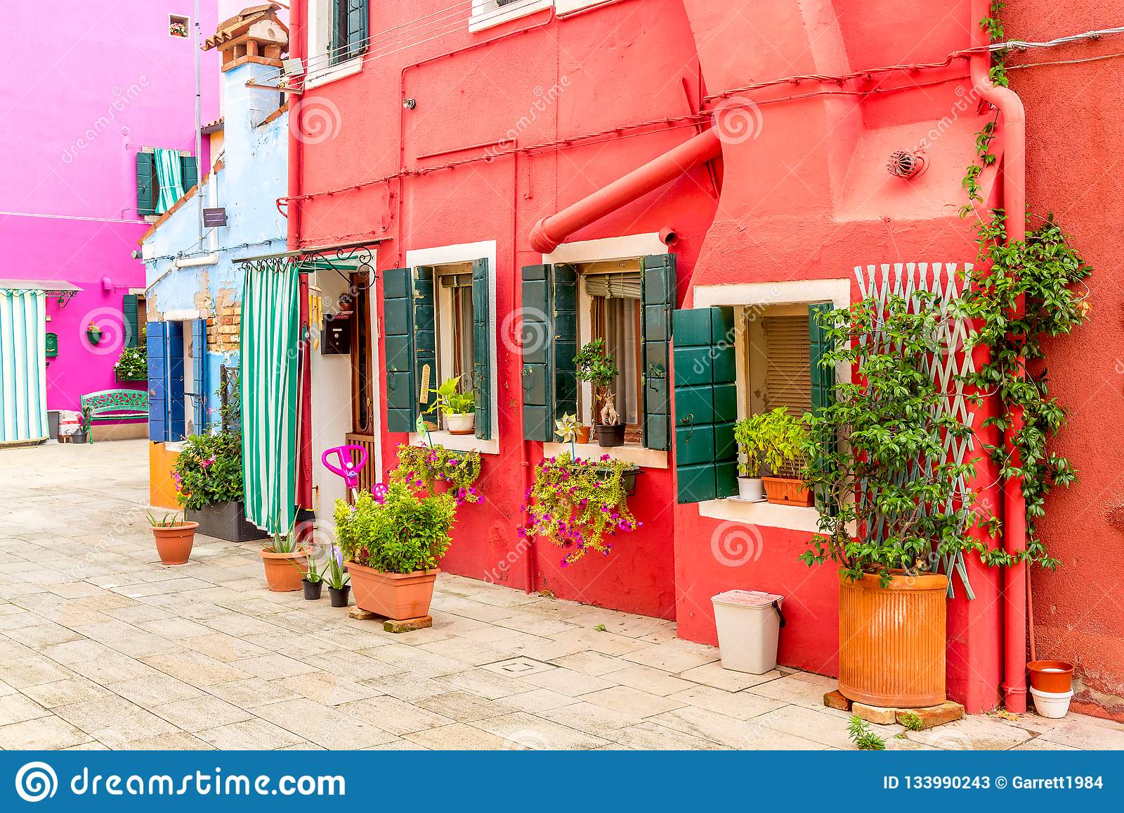 Härligt färgrikt rött litet hus med växter i den Burano ön nära Venedig, Italien