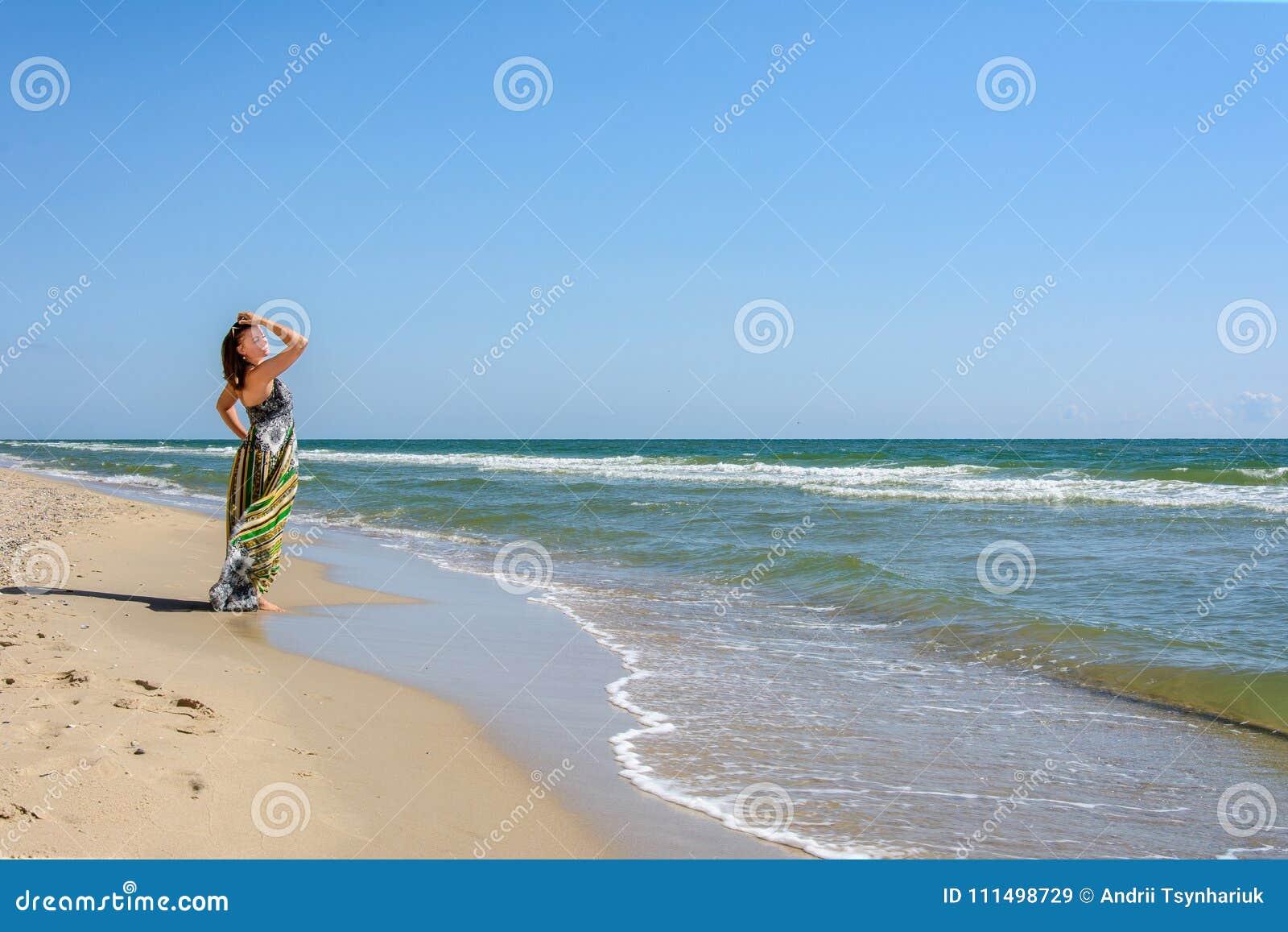 Härligt flickaanseende på stranden av Blacket Sea i solglasögon och klänningar
