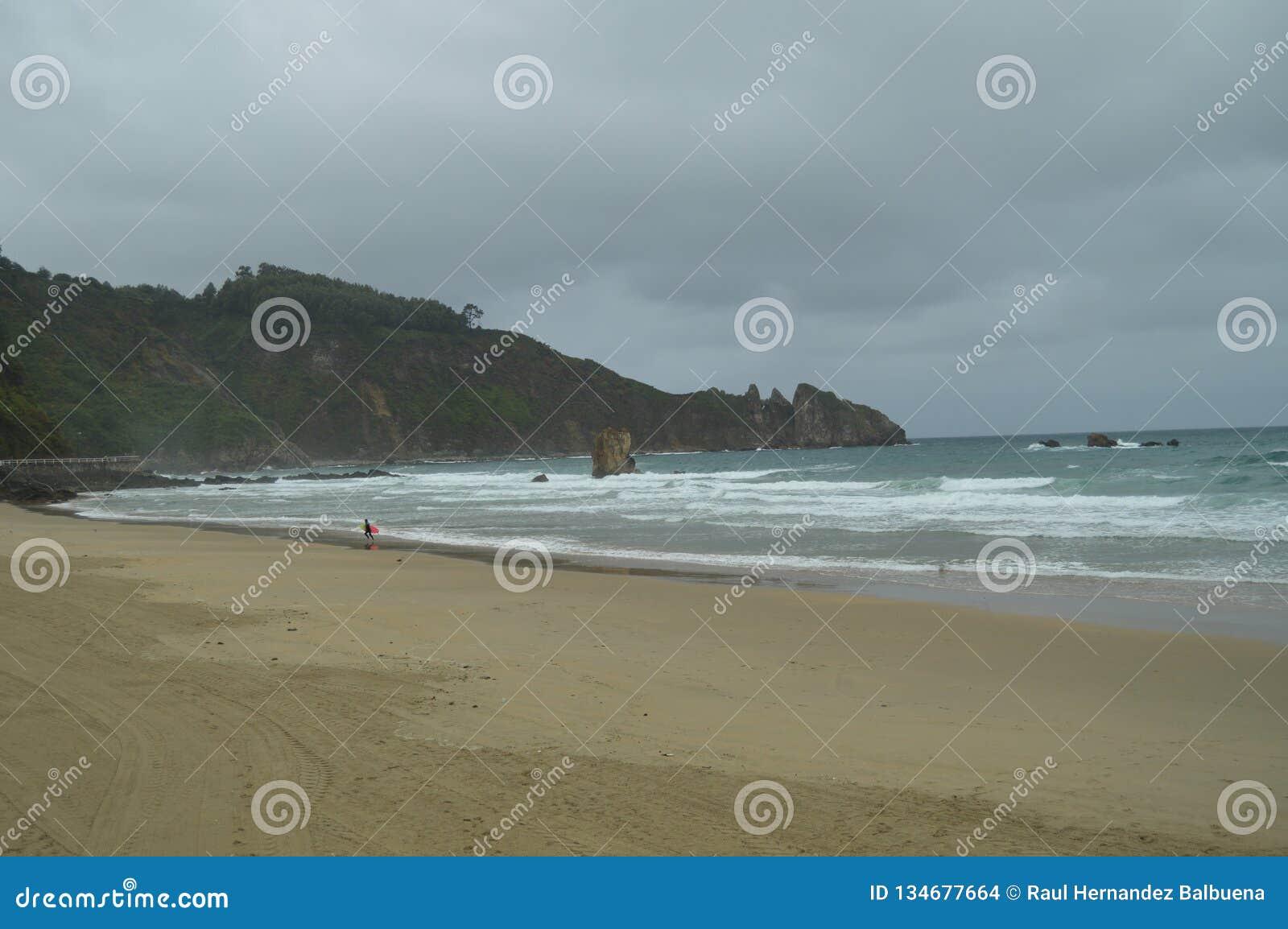 Härligt foto av stranden för El Aguilar på en regnig dag