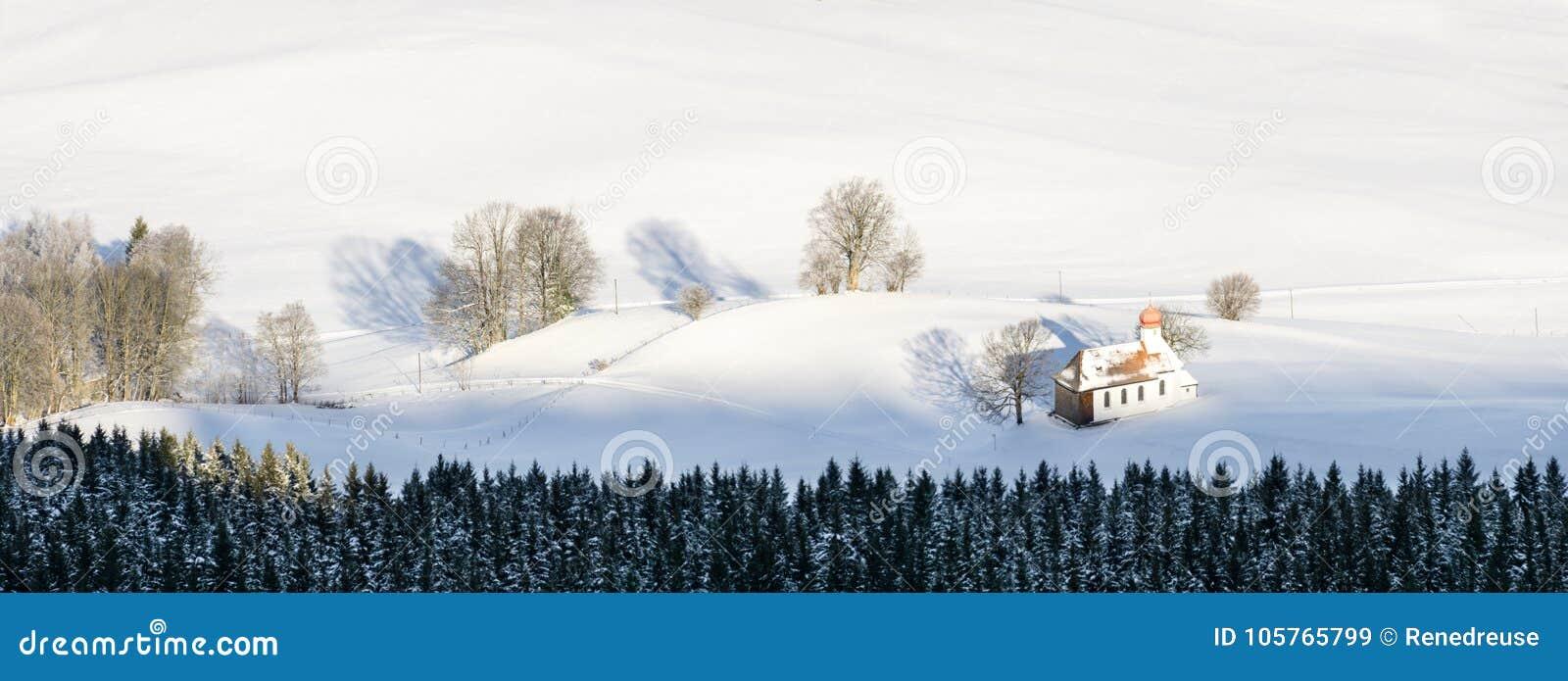 Härligt kapell i älskvärd lantlig bygd på snöig vintersoluppgång som ses från över Weitnau Allgau, Bayern, Tyskland
